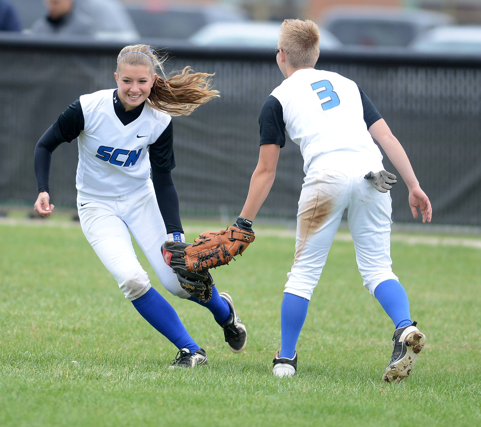 St. Charles North's Delaney Olinger, left, gives a low five to teammate Andrea Beal after Beal made a big catch during Tuesday's game in St. Charles.