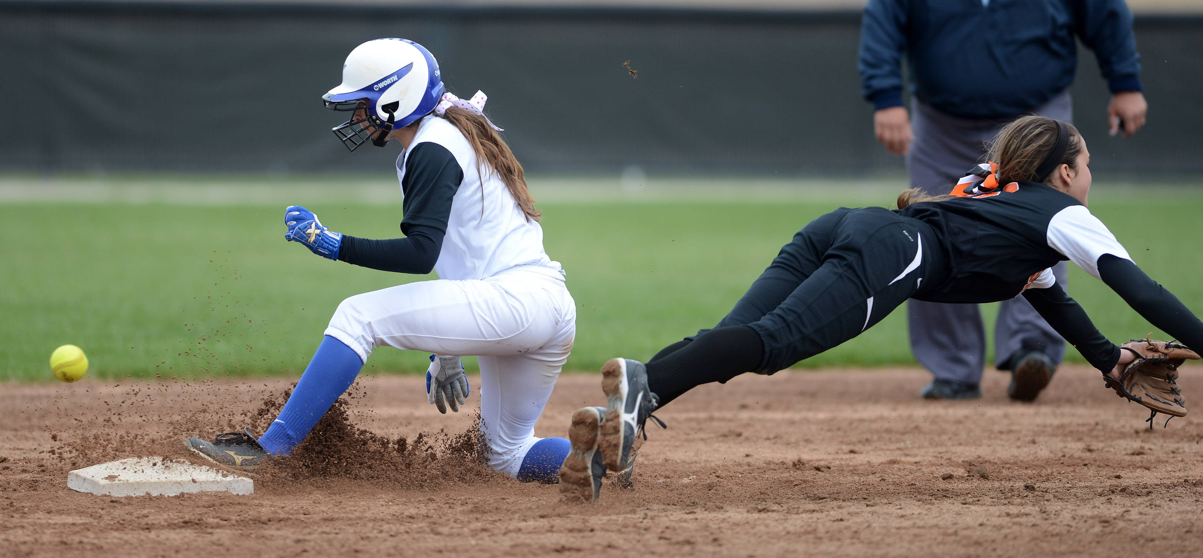 St. Charles North's Sabrina Rabin slides safely into second with a steal as the throw gets past a diving Olivia Cheatham.