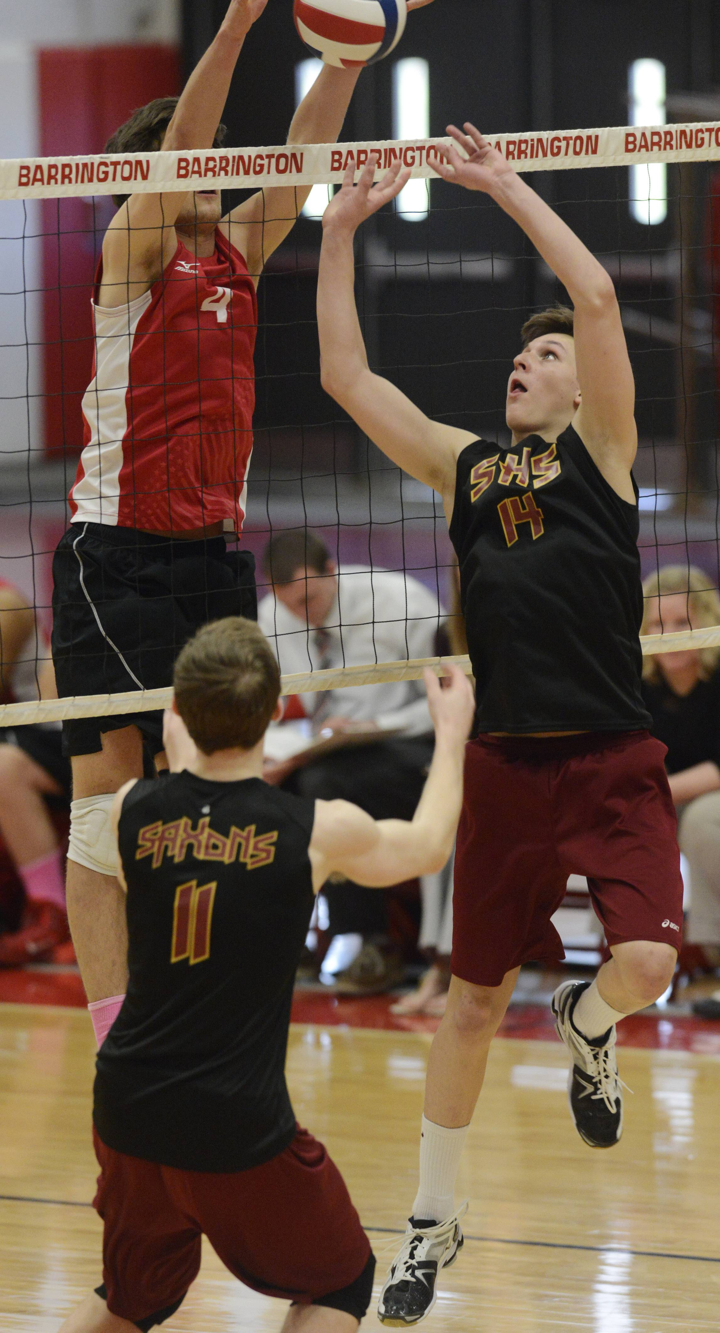 Schaumburg's Erik Kirschbaum, right, tries to tip the ball past Barrington's Adam Glader during Tuesday's volleyball match.