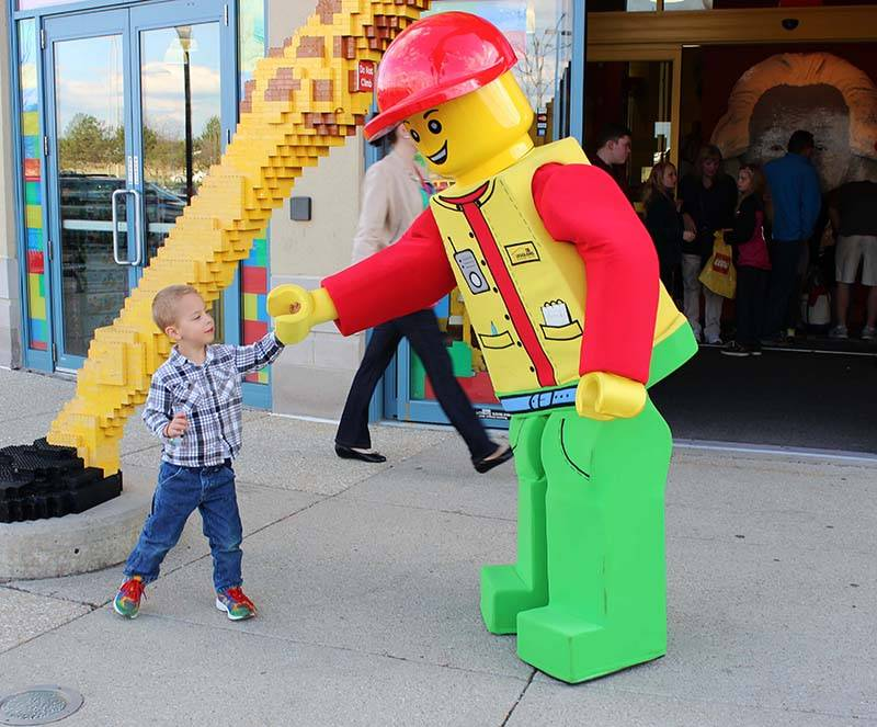 An Easter Seals guest poses for a photo with Legoland Discovery Center Chicago's Bertie Minifigure.