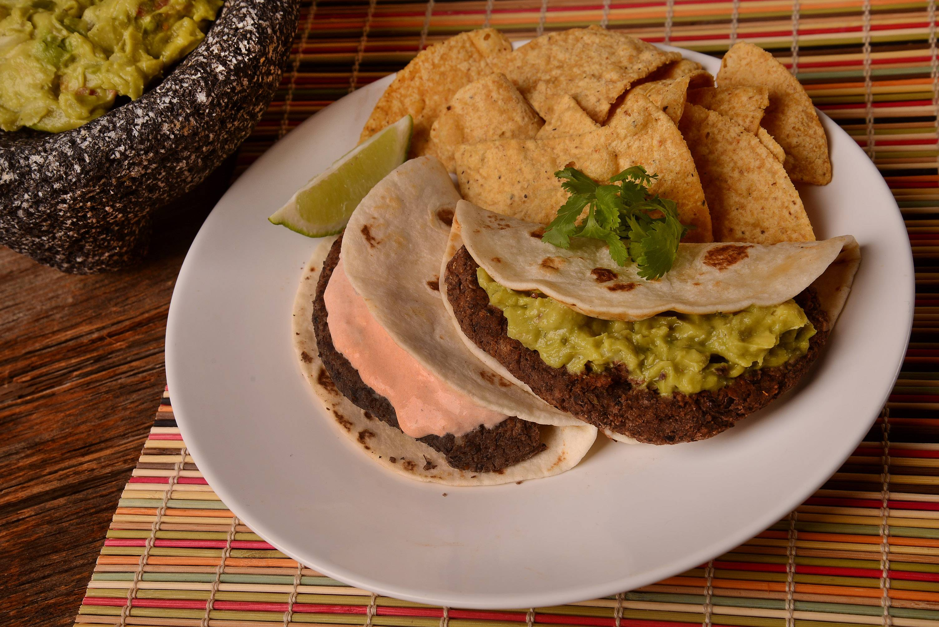 For a vegetarian spin on burgers, try these mildly spicy black bean patties nestled between tortillas and topped with creamy salsa or guacamole.