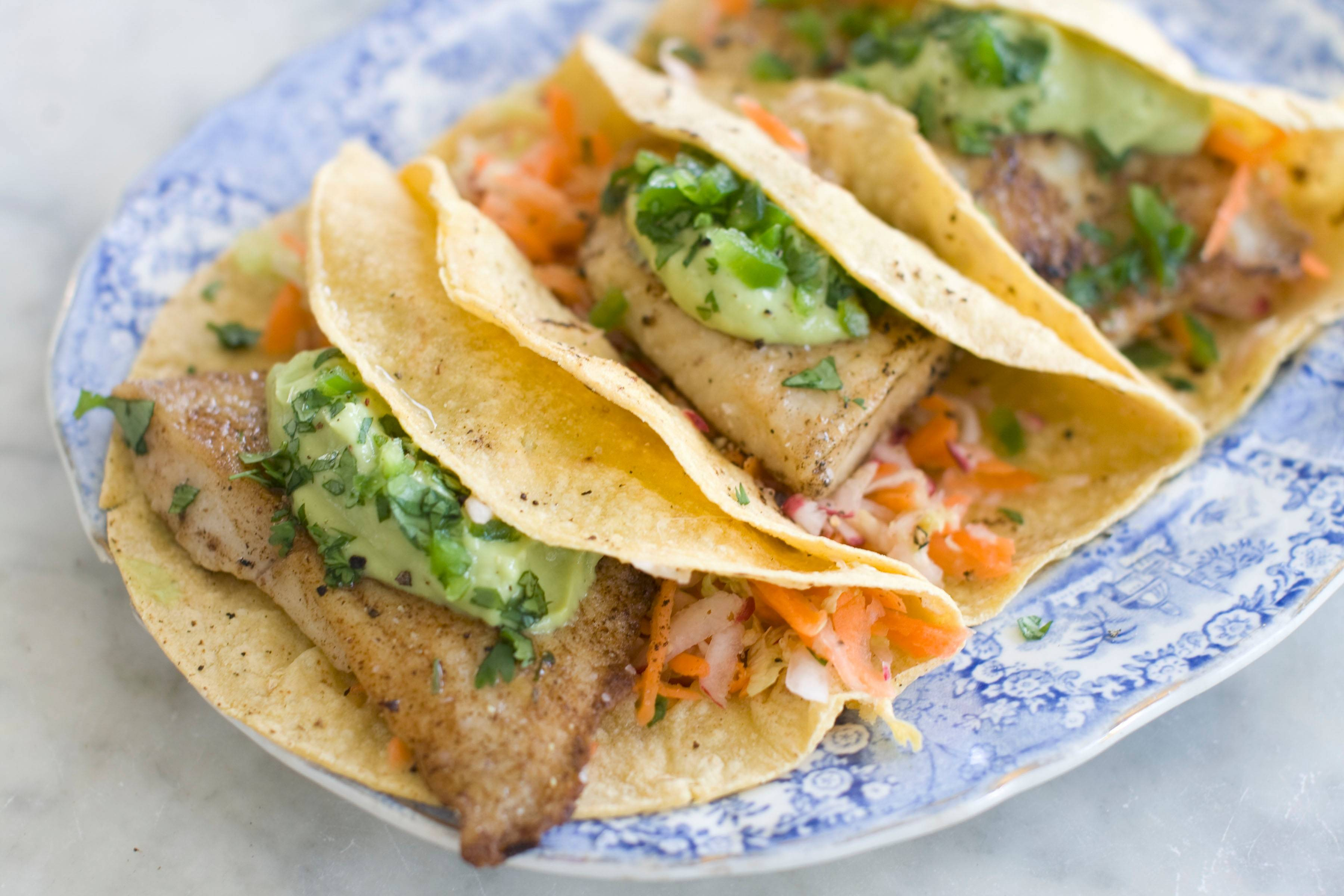 Avocado-buttermilk cream and carro slaw make tilapia tacos all the more tasty.