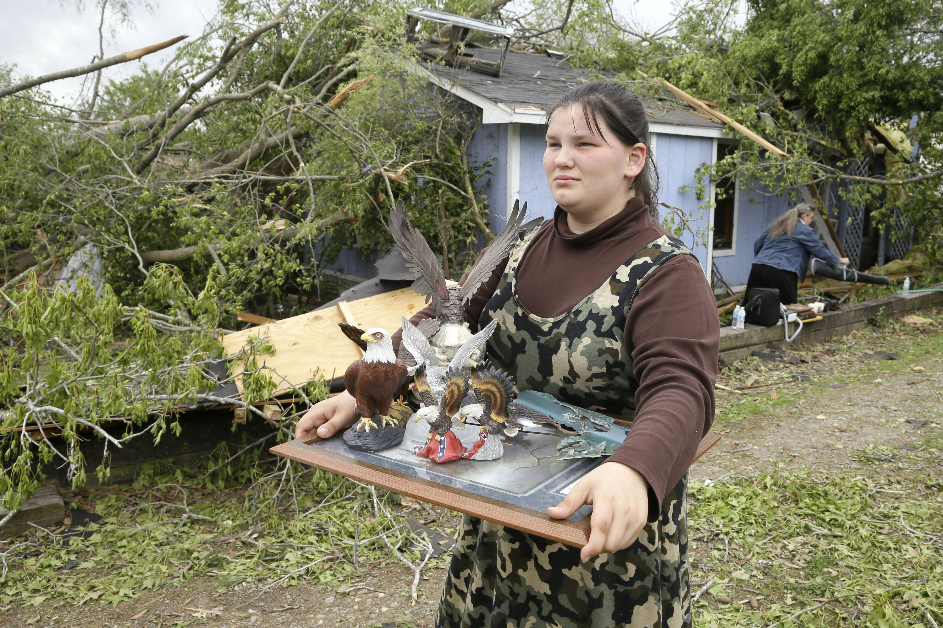 Rosie Hollingshead, 15, carries her father's collection of eagle figurines from her tornado-damaged home in Mayflower, Ark., Tuesday, April 29, 2014.