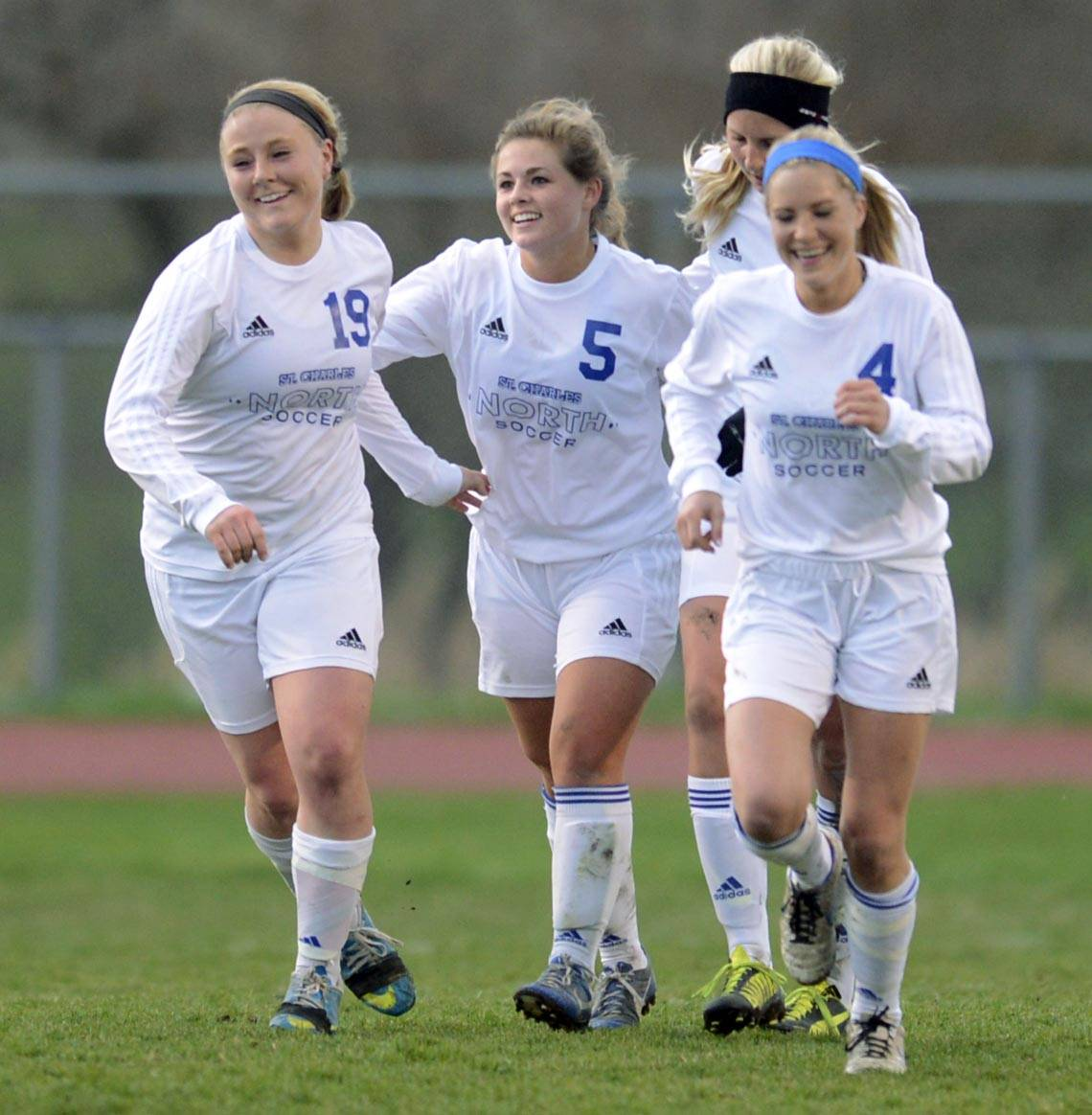St. Charles North's Hanna Durocher, 5, is surrounded by teammates after her goal against Geneva Wednesday in St. Charles.