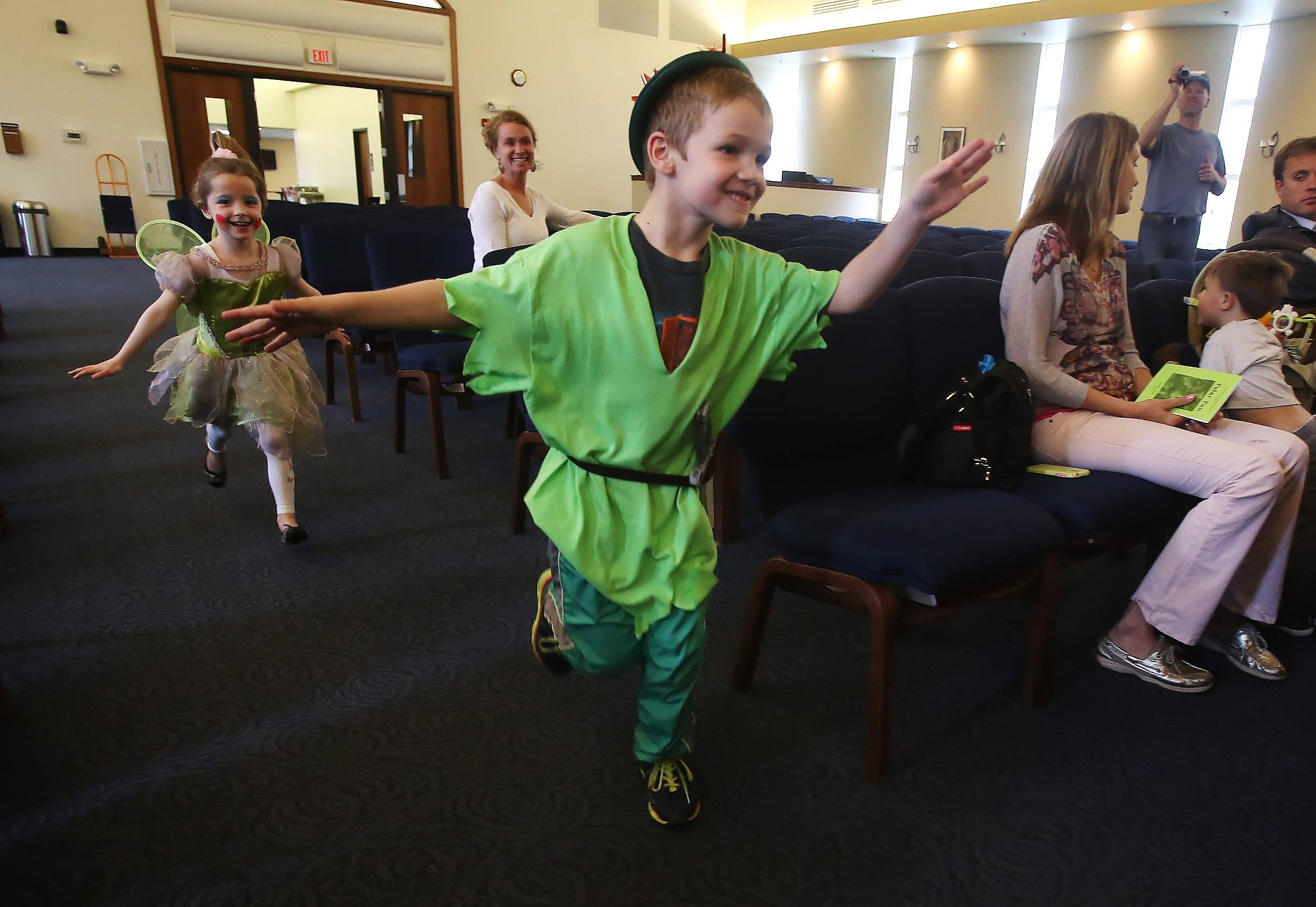 "Peter Pan, played by Casey Whitebread, and Tinker Bell, played by Scarlett Meyer, ""fly"" around the audience Wednesday as Libertyville Cooperative Preschool students perform ""Peter Pan"" at Trinity Community Church in Libertyville. The students performed, worked on the background, put on their own makeup and helped design the tickets and programs."