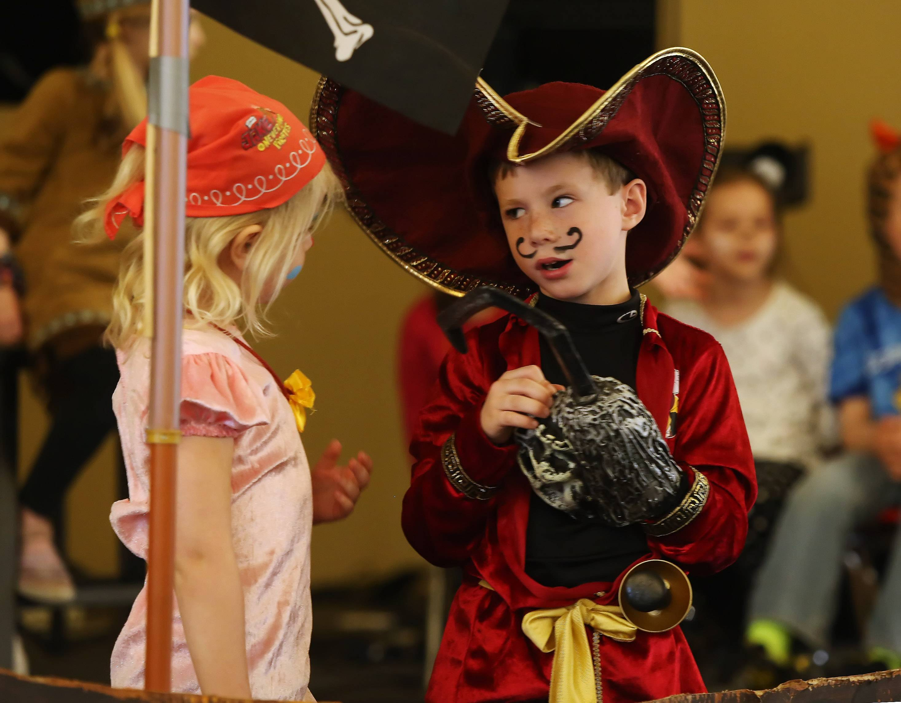"Captain Hook, played by Ben Oswald, talks with Miss Smee the Pirate, played by Spencer Schreiber, as Libertyville Cooperative Preschool students perform ""Peter Pan"" Wednesday at Trinity Community Church in Libertyville. The students performed, worked on the background, put on their own makeup and helped design the tickets and programs."