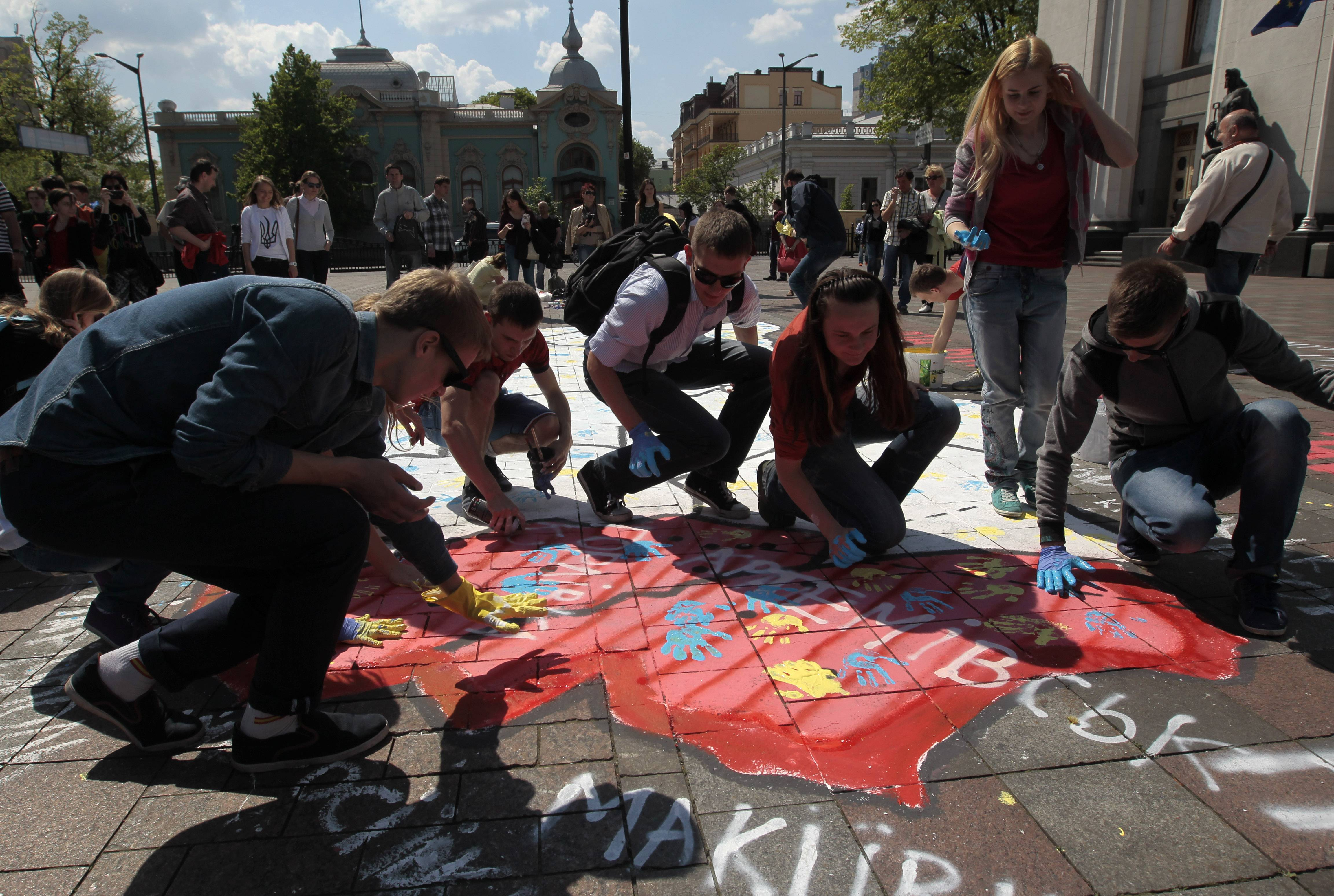 Activists leave their blue and yellow palm prints on the territory, painted in red, of a map of eastern Ukraine to show the unity of the country in Kiev, Ukraine, Wednesday, April 30, 2014.