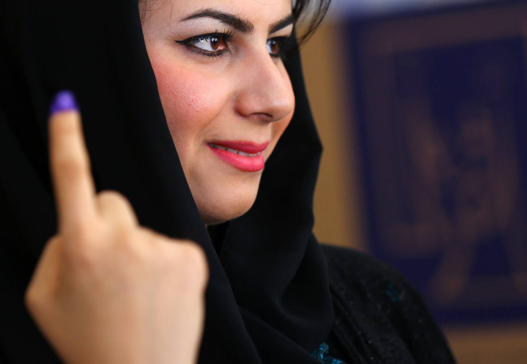 An Iraqi Kurdish woman shows her ink-stained finger after casting her vote at a polling station in Irbil, north of Baghdad, Iraq, Wednesday, April 30, 2014.