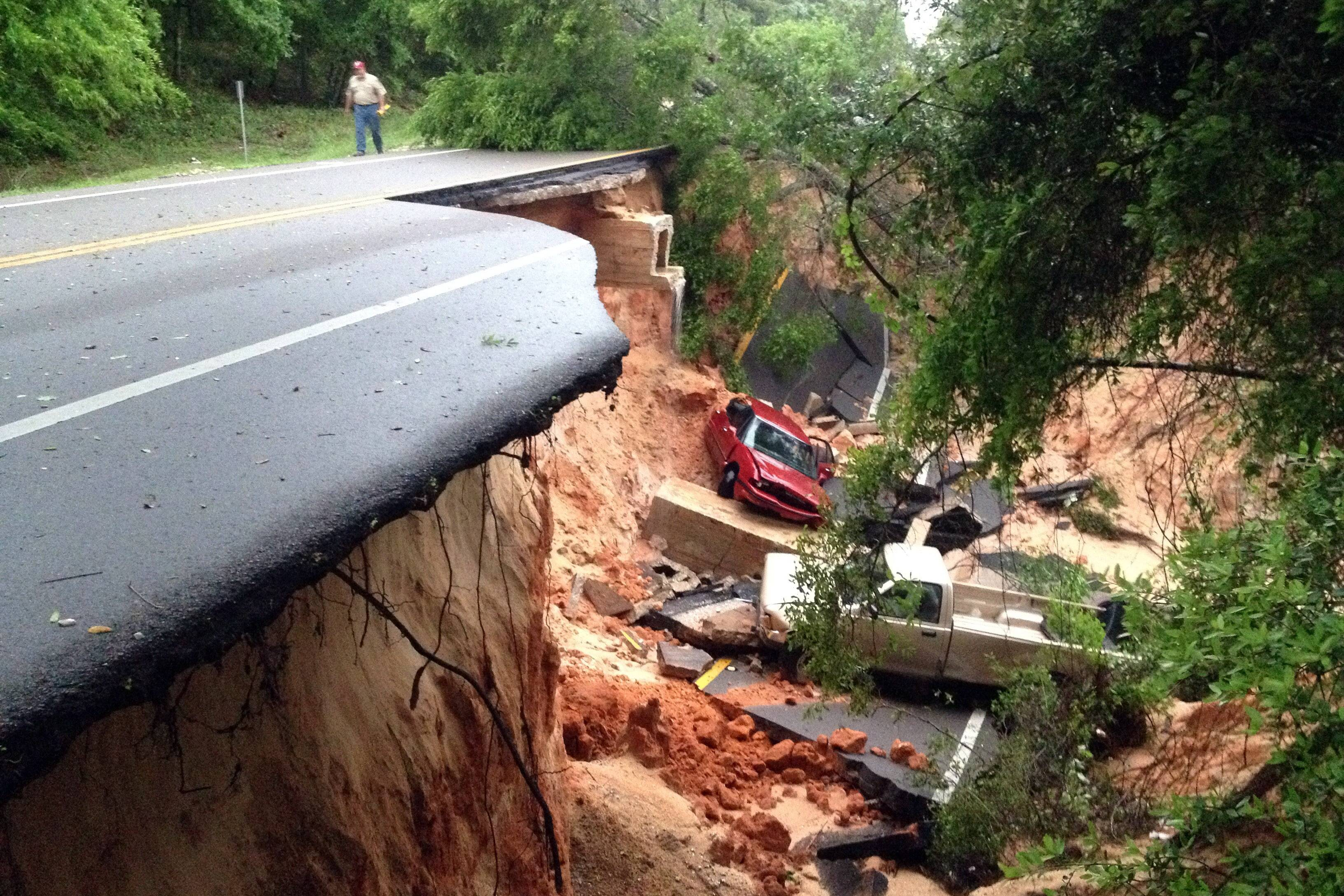 Vehicles rest at the bottom of a ravine after the Scenic Highway collapsed near Pensacola, Fla., Wednesday. Heavy rains and flooding have left people stranded in houses and cars in the Florida Panhandle and along the Alabama coast.