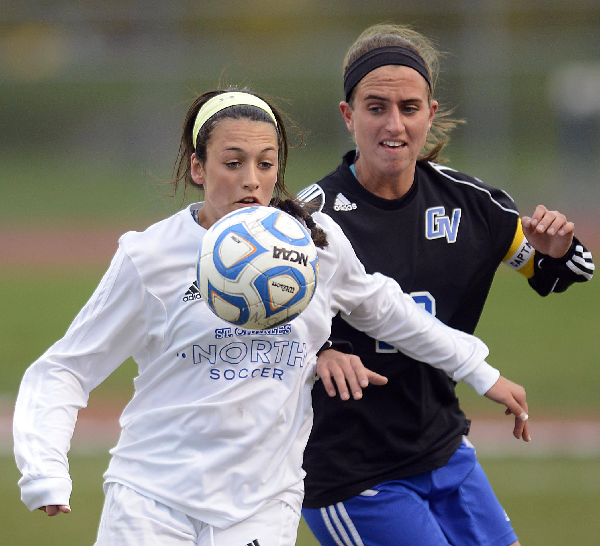 St. Charles North's Ashlyn Walter eyes the ball and holds off Geneva's Molly Stanfa Wednesday in St. Charles.