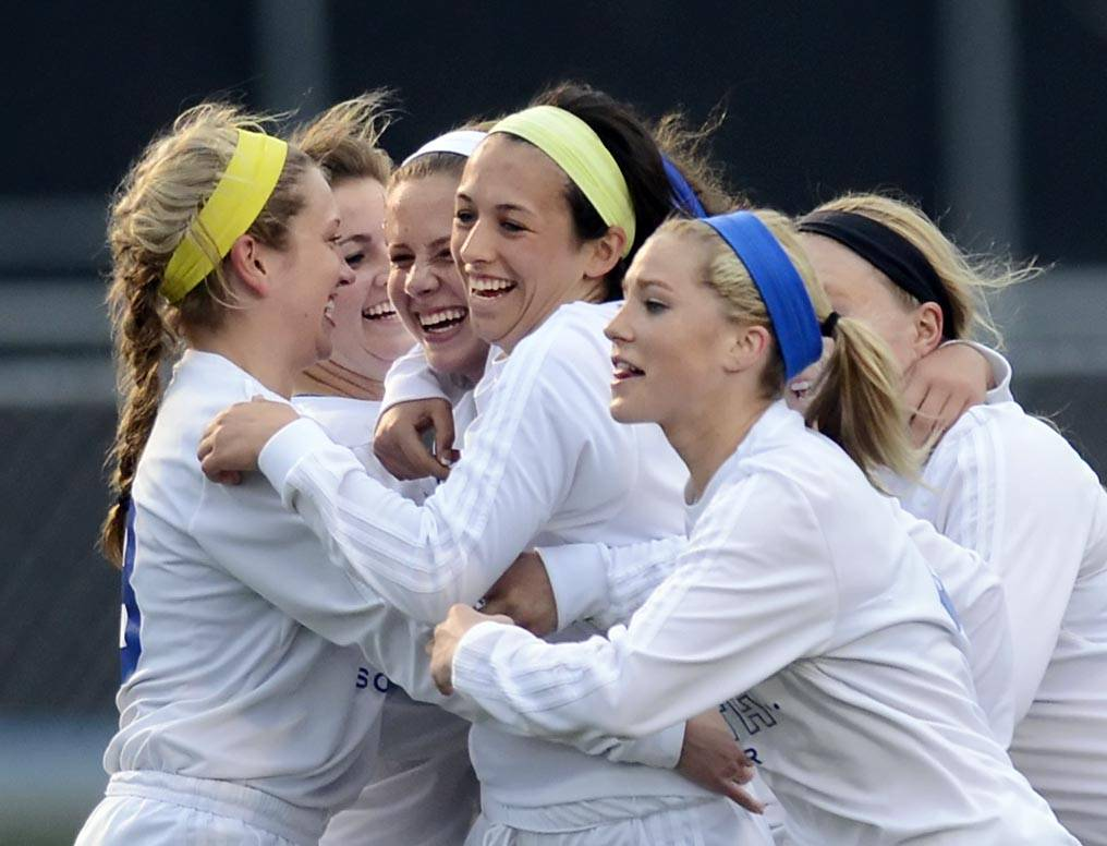 St. Charles North's Alyssa Brandt, white headband, is surrounded by teammates after her goal against Geneva Wednesday in St. Charles.