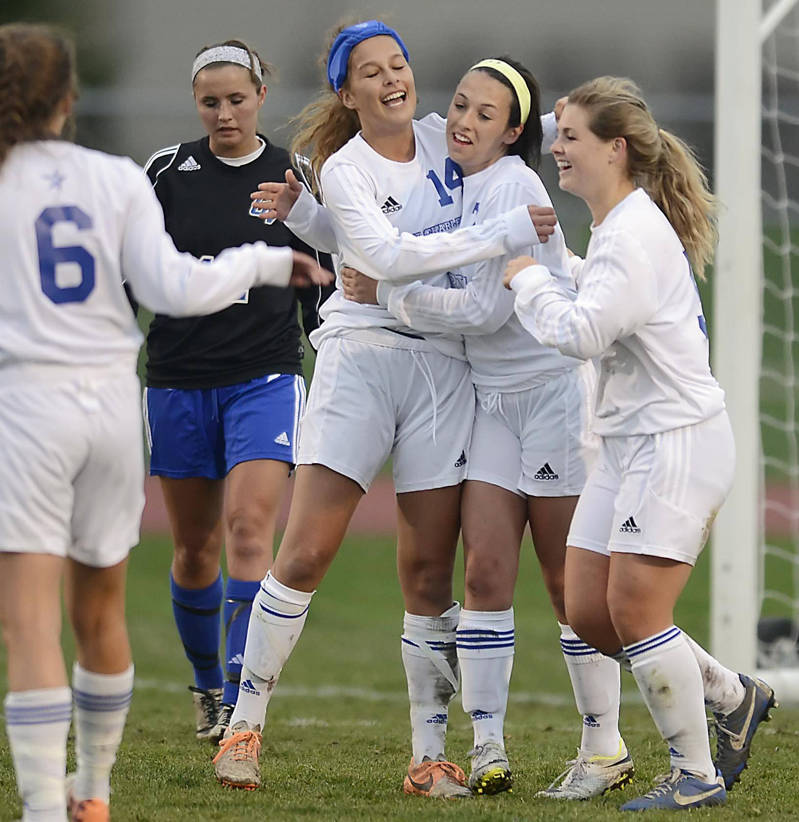St. Charles North's Ashlyn Walter, second from right, is hugged by teammates after her first half goal against Geneva Wednesday in St. Charles.