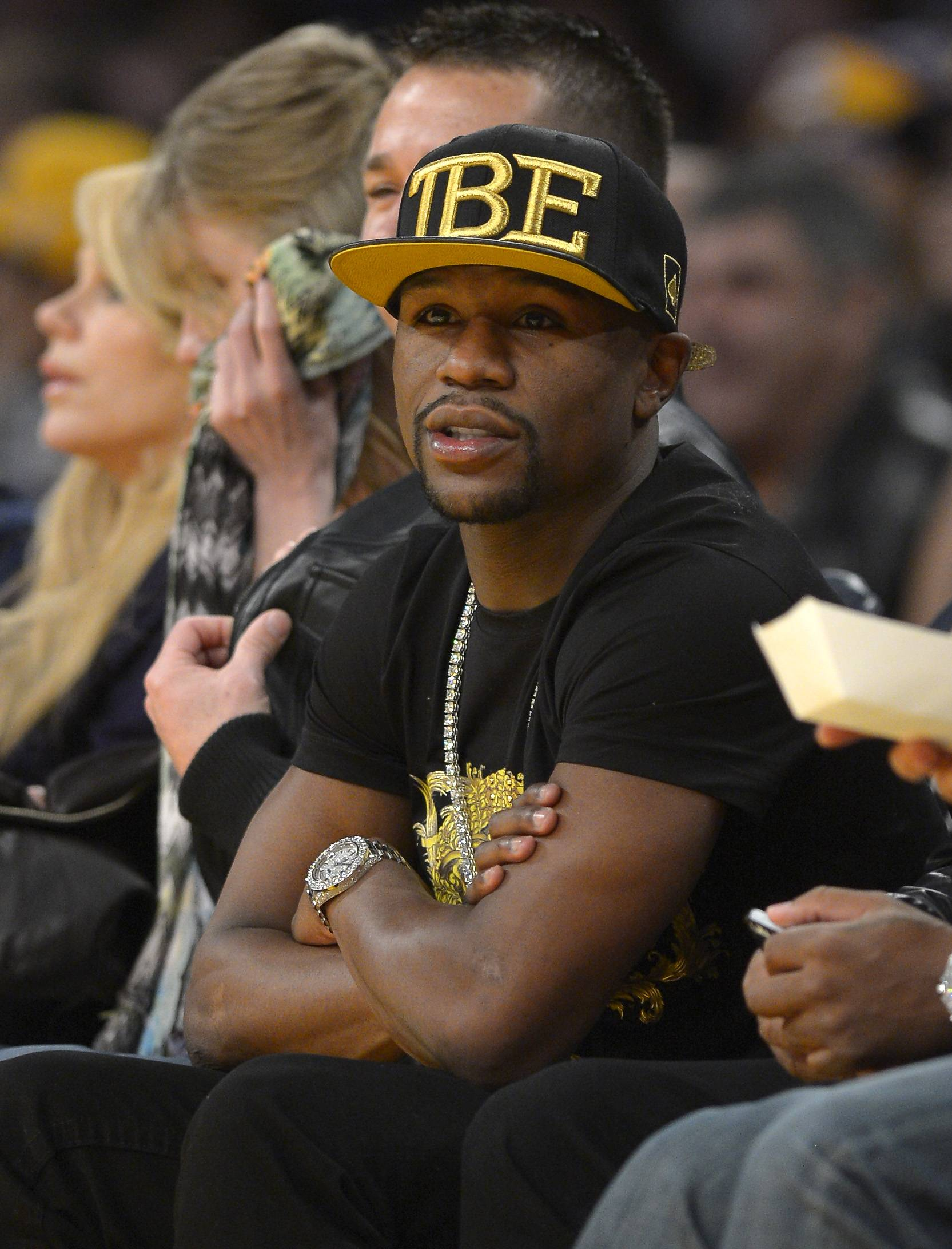 FILE - In this Nov. 24, 2013, file photo, Boxer Floyd Mayweather Jr. watches the Los Angeles Lakers play the Sacramento Kings during the first half of an NBA basketball game in Los Angeles. If Donald Sterling is compelled to sell the Los Angeles Clippers, the list of potential buyers will have more stars than the team's roster. Mayweather Jr. wants to form a group to buy the team.