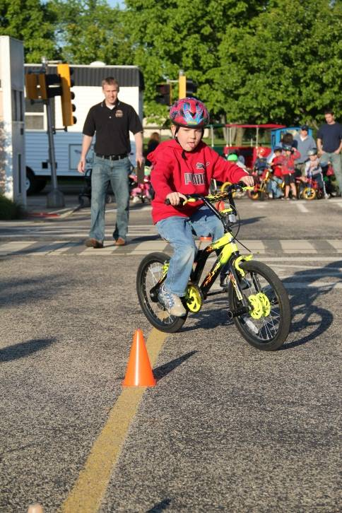 A boy shows off his cycling skills by riding through cones.Schaumburg Park District