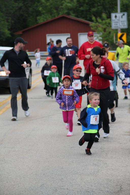Children race in the 1/2 Mile Youth Run as parents encourage them.Schaumburg Park District
