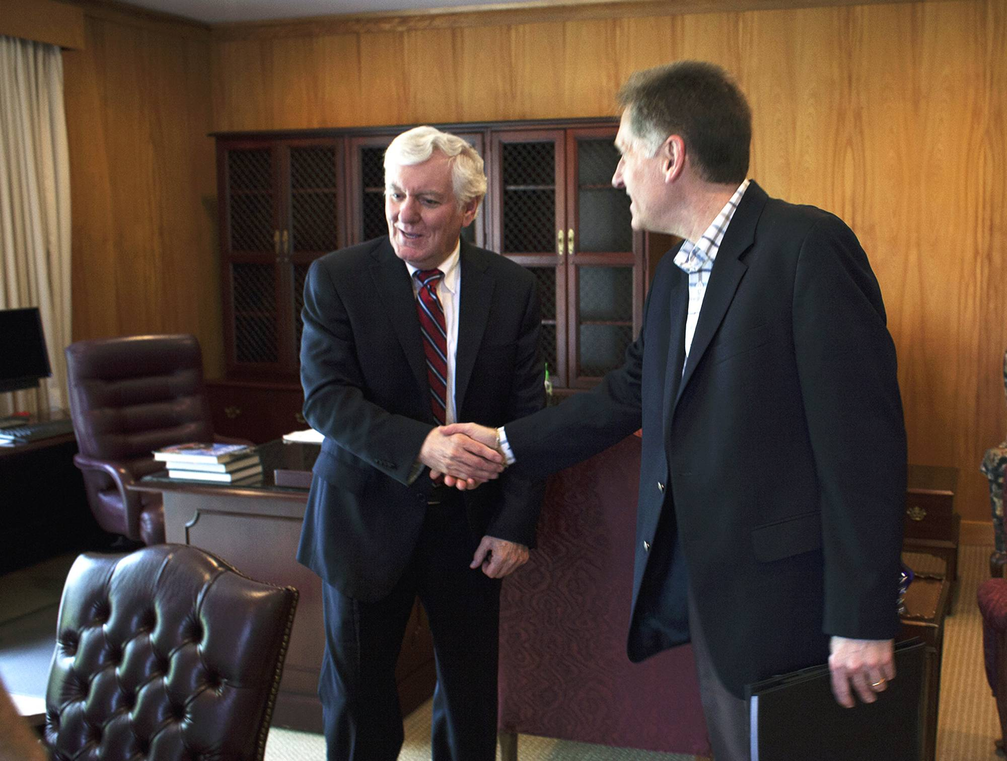 Glenn Poshard, left, shakes hands with incoming SIU president Randy Dunn on Wednesday in Carbondale. Poshard officially retired Wednesday but will stay on through June as a consultant to his successor.