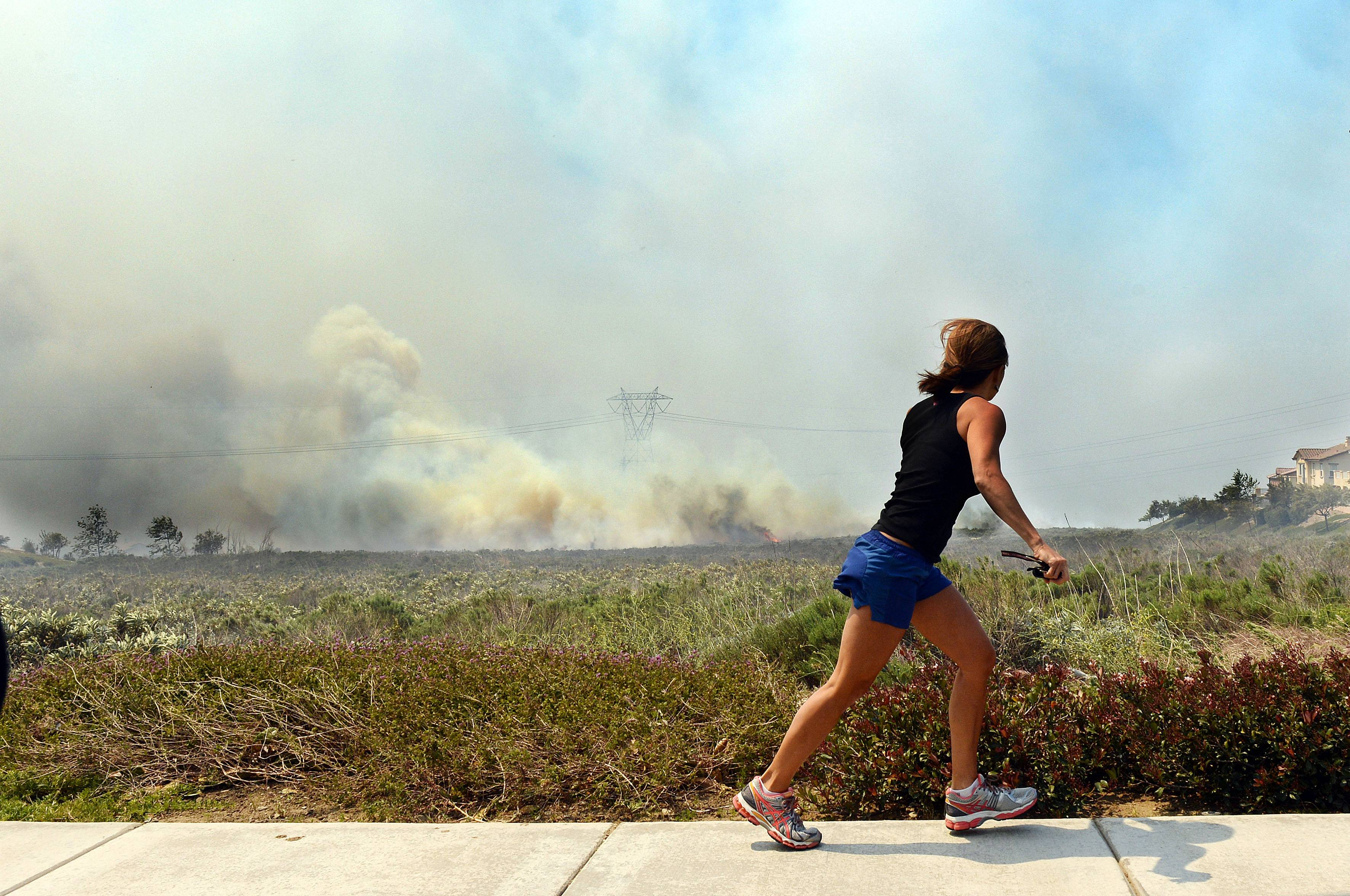 A resident talks on her phone as she watches the Etiwanda Fire in Rancho Cucamonga, Calif., Wednesday, April 30, 2014.