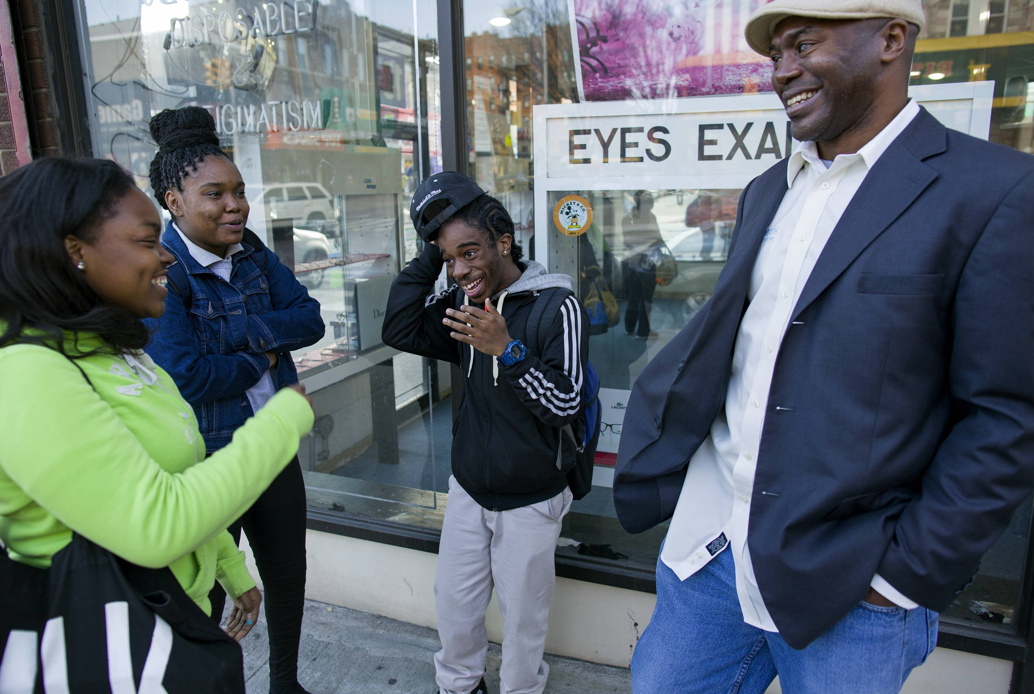 Dr. Kai Smith, right, former gang member and now founder and Executive Director of GRAAFICS (Gang Diversion, reentry and Absent Father Intervention Center), talks with GRAAFICS students (from left) Tyasia Blair, 16, of East New York, Keeozel Saul, 16, and Devon Collins, 16, of East New York, in the Brownsville neighborhood of Brooklyn, N.Y.