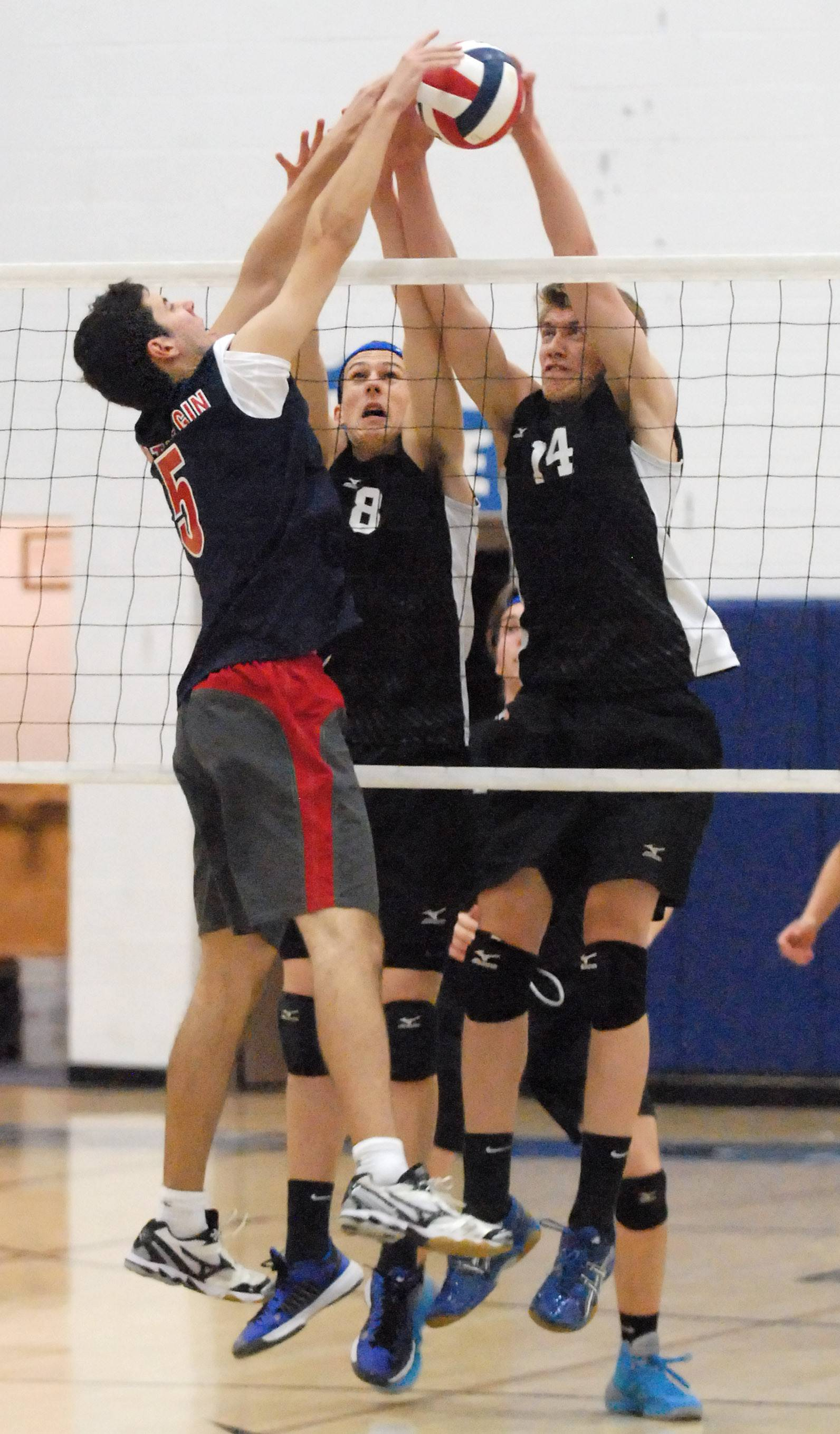 South Elgin's Dan Gibadlo tips the ball over the net as St. Charles North's Jeff Rollins (8) and Jack Bujko (14) defend at the net in the first match on Thursday, May 1.