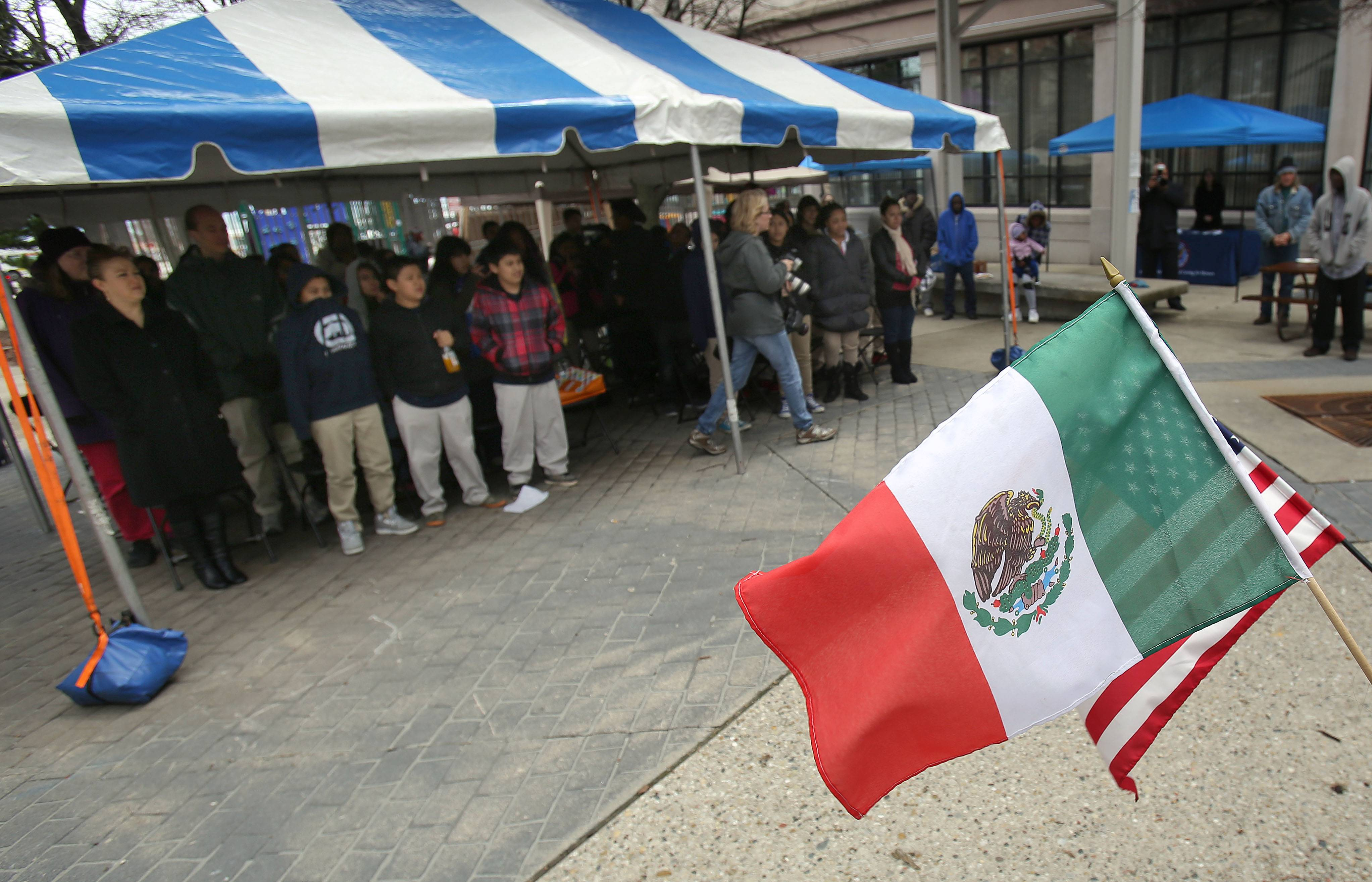 People stand for the Mexican and U.S. national anthems during Thursday's Cinco de Mayo celebration at the College of Lake County's Lakeshore Campus in downtown Waukegan.