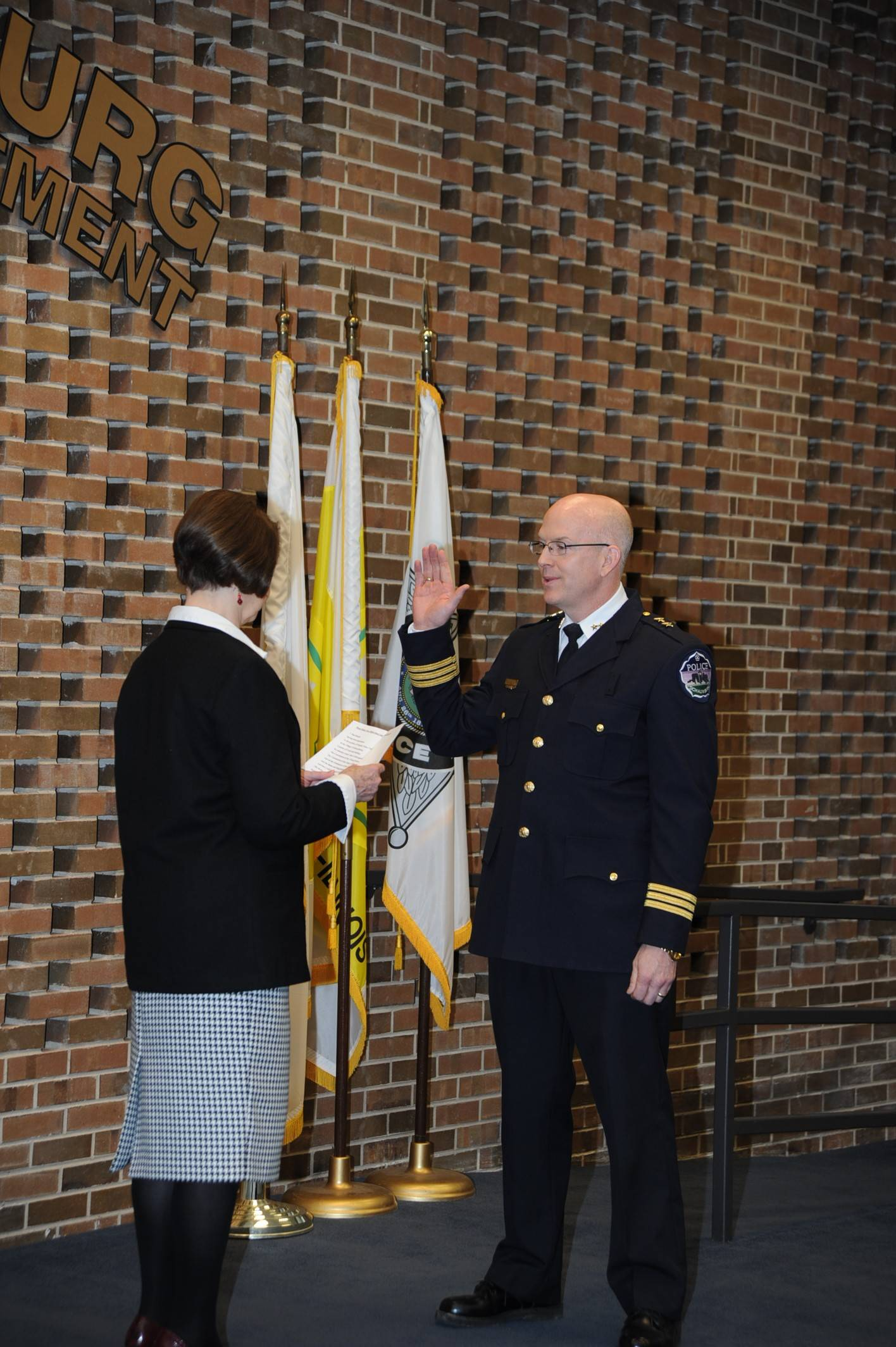 Schaumburg Village Clerk Marilyn Karr, left, swears in new Deputy Police Chief Dan Roach on Thursday. Roach's promotion from commander of investigations to deputy chief completes the restructuring of the department's command structure, which began after three undercover officers' arrests last year.