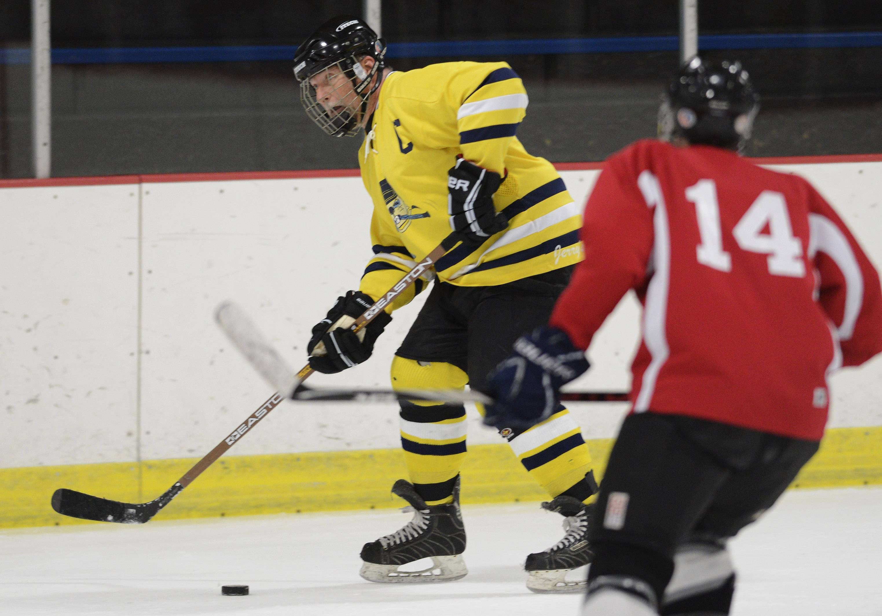 "Gerry Dudziak of Rolling Meadows, the captain of ""Gerry's Kids,"" an over-40 hockey team, passes the puck as an opponent closes in during a game in Park Ridge."