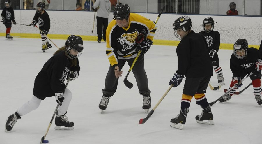 Dudziak instructs his granddaughter, Nina Griffiths, 8, left, also of Rolling Meadows, during a Mite Majors hockey practice at the West Meadows Ice Arena.