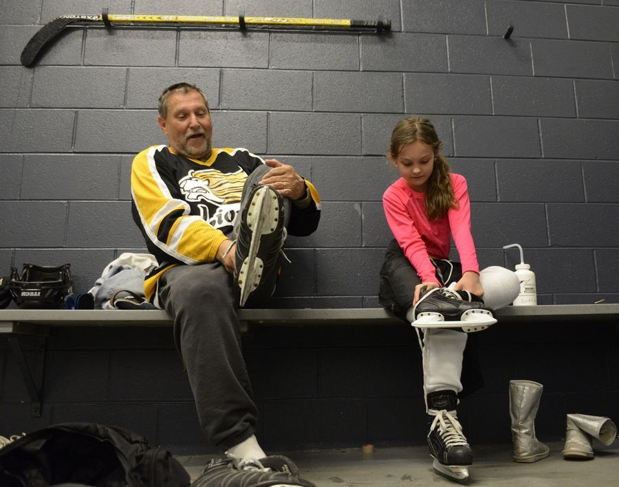 Dudziak and his granddaughter, Nina, remove their skates after practice at the West Meadows Ice Arena.