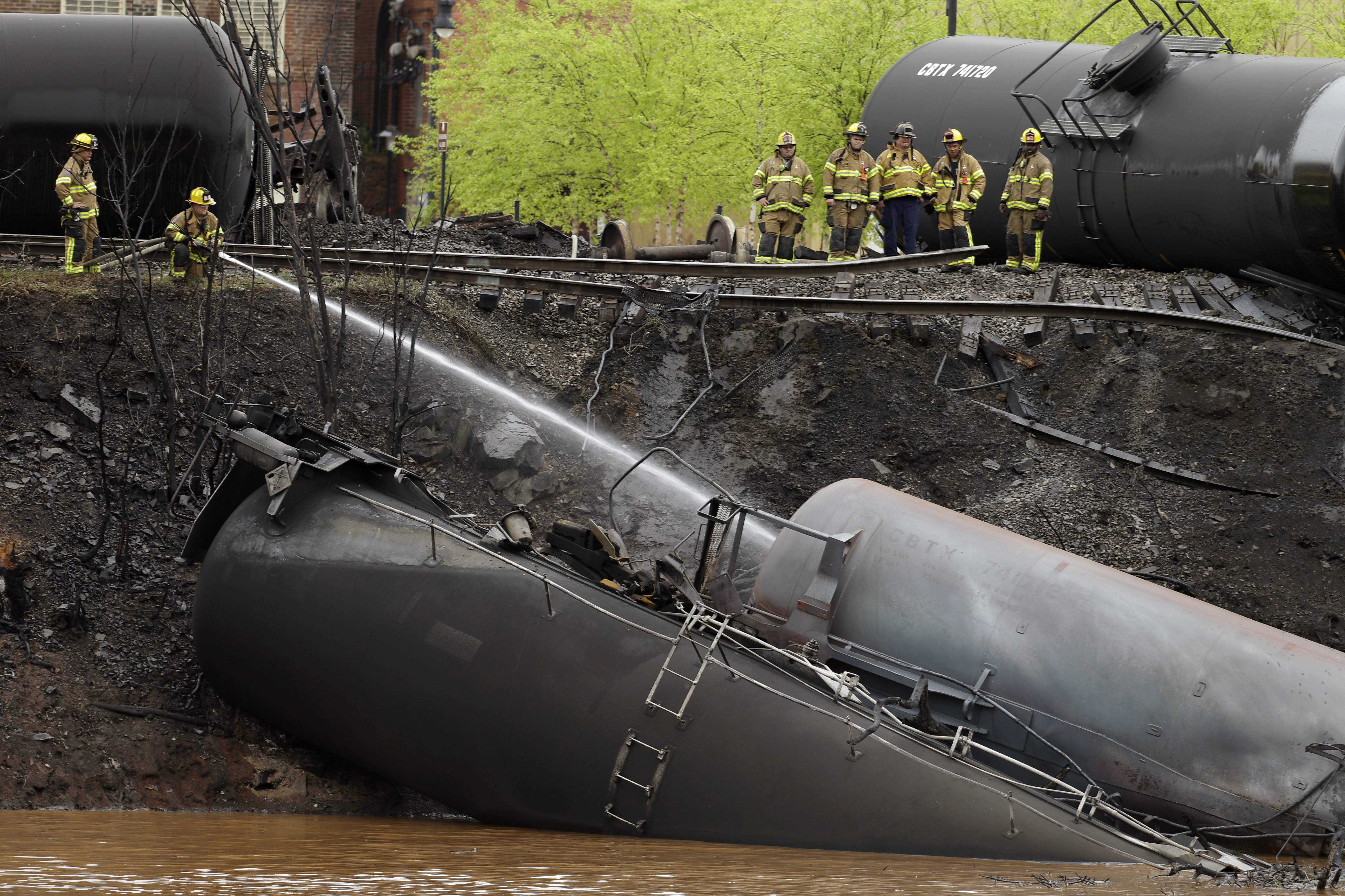 Firefighters and rescue workers work along the tracks where several CSX tanker cars carrying crude oil derailed and caught fire along the James River near downtown in Lynchburg, Va., Wednesday, April 30, 2014.