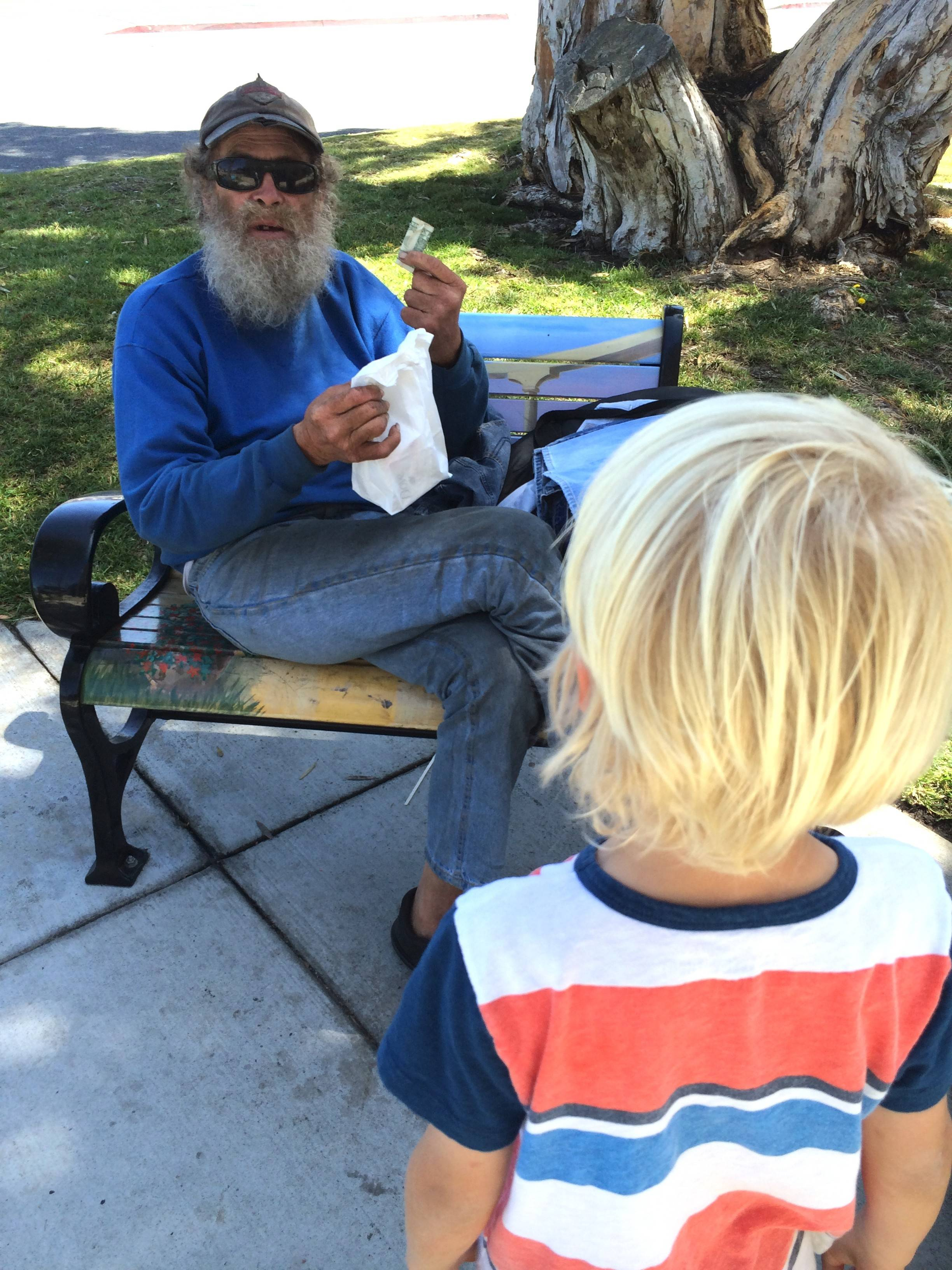 "As part of a kindness campaign to honor the memory of Sadie Elizabeth McCann of Des Plaines, young Aidric Zohlen gives a ""self-help"" bag to a homeless man in Redondo Beach, Calif."