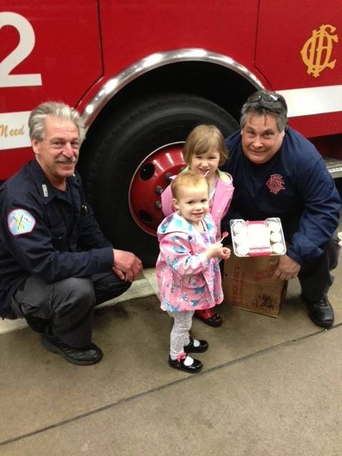 Sisters Hannah (front) and McKenzie Behling deliver cupcakes to local firefighters as part of a campaign to perform good deeds in the memory of Sadie McCann of Des Plaines.