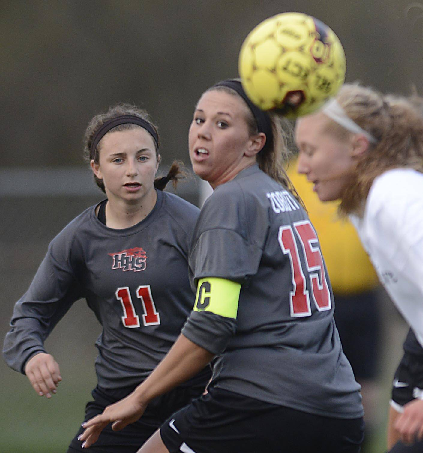 The ball bounces past Cary-Grove's Emily Petersen and Huntley's Taryn Jakubowski and Rachel Zobott Thursday in Cary.