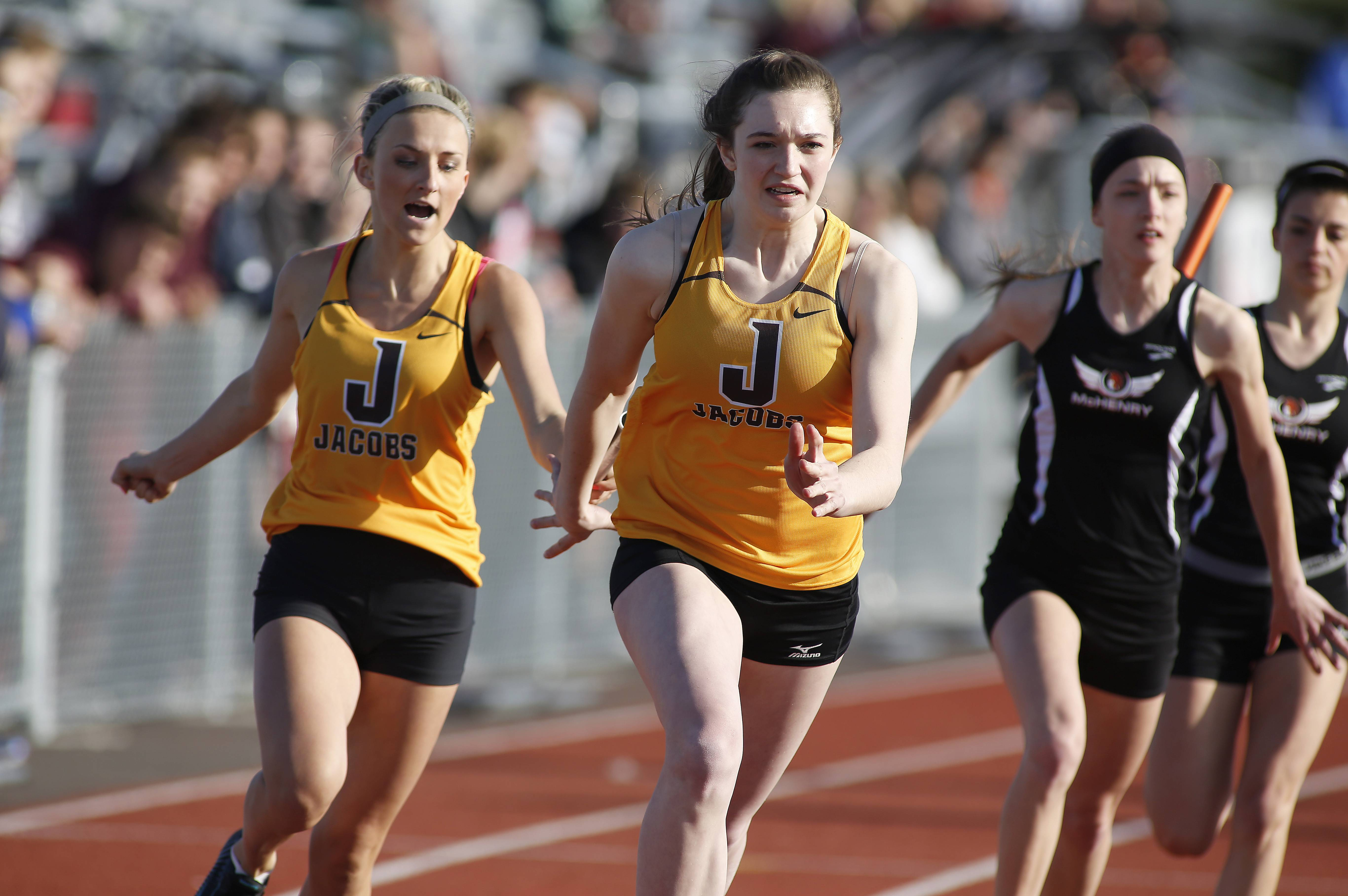 Jacob's Lexi Post, left, and Rachael Holstein hand off the baton in the 4x100 relay during the McHenry County Track and Field Championships last Friday in Huntley.