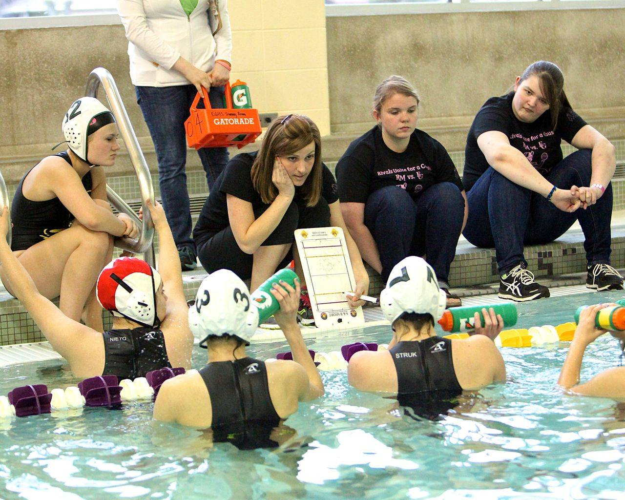Alexa Rodheim, center, Elk Grove High School water polo coach, works with her team last week at a meet with Rolling Meadows. She's battling from an aggressive form of breast cancer and students are rallying to support her fight.