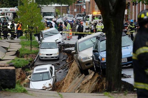 A sidewalk and retaining wall in Baltimore's Charles Village neighborhood buckled and caved in Wednesday afternoon, swallowing a streetlight and more than half a dozen cars. No one was injured.