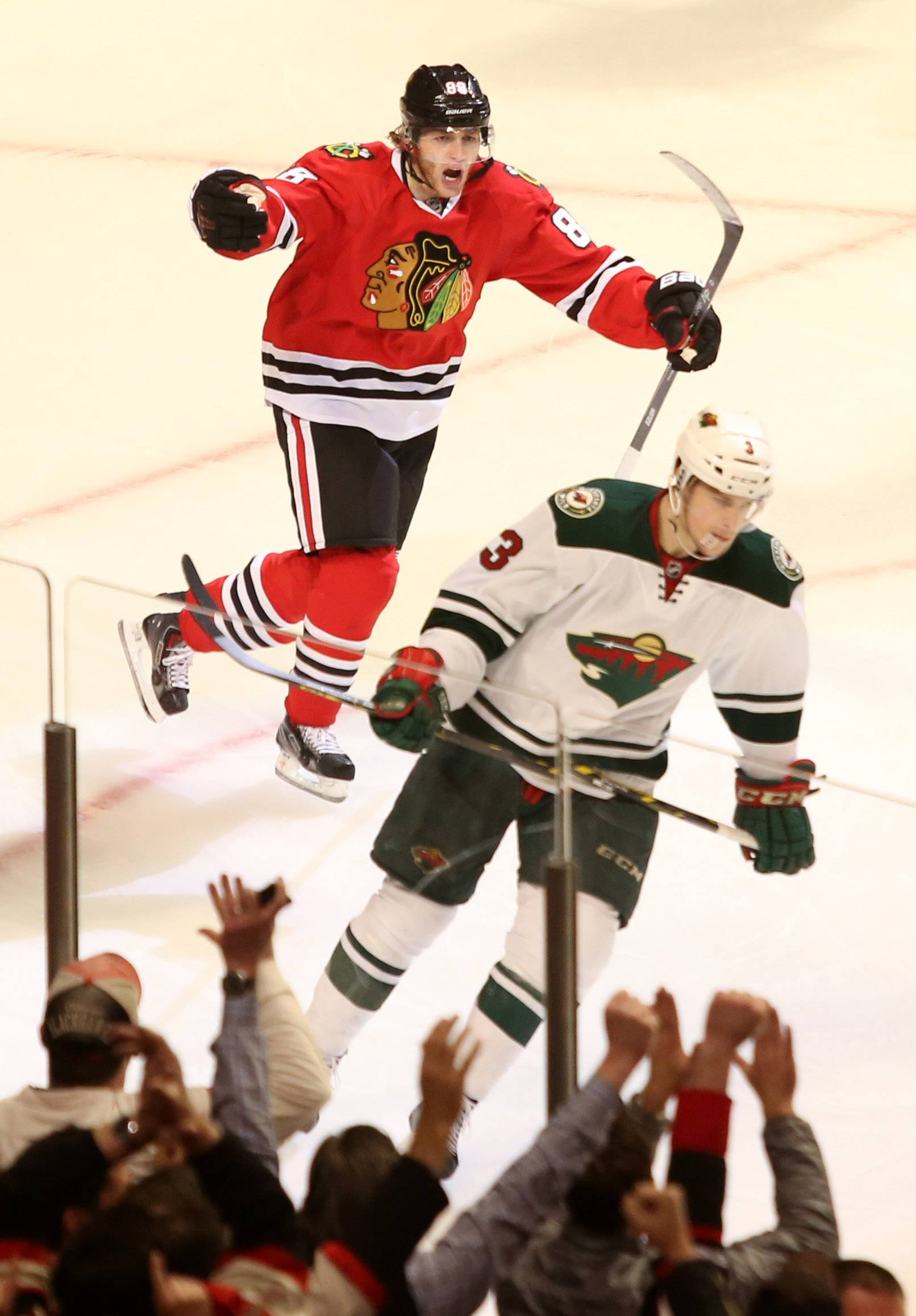 Daniel White/dwhite@dailyherald.comPatrick Kane celebrates his game leading third period goal during a 5-2 win over the Wild. Charlie Coyle skates away from the play.