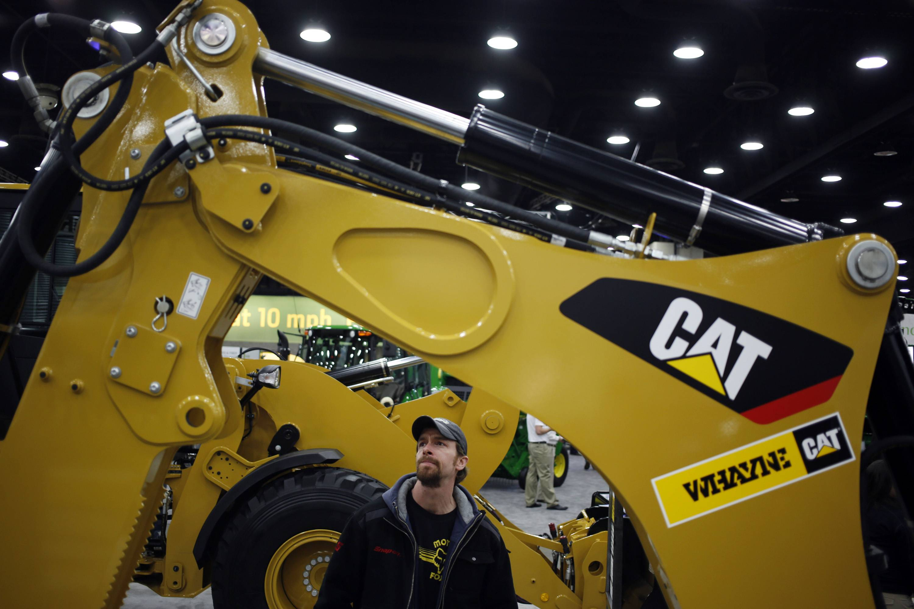 An attendee examines a Caterpillar Inc. backhoe loader at the National Farm Machinery Show in Louisville.