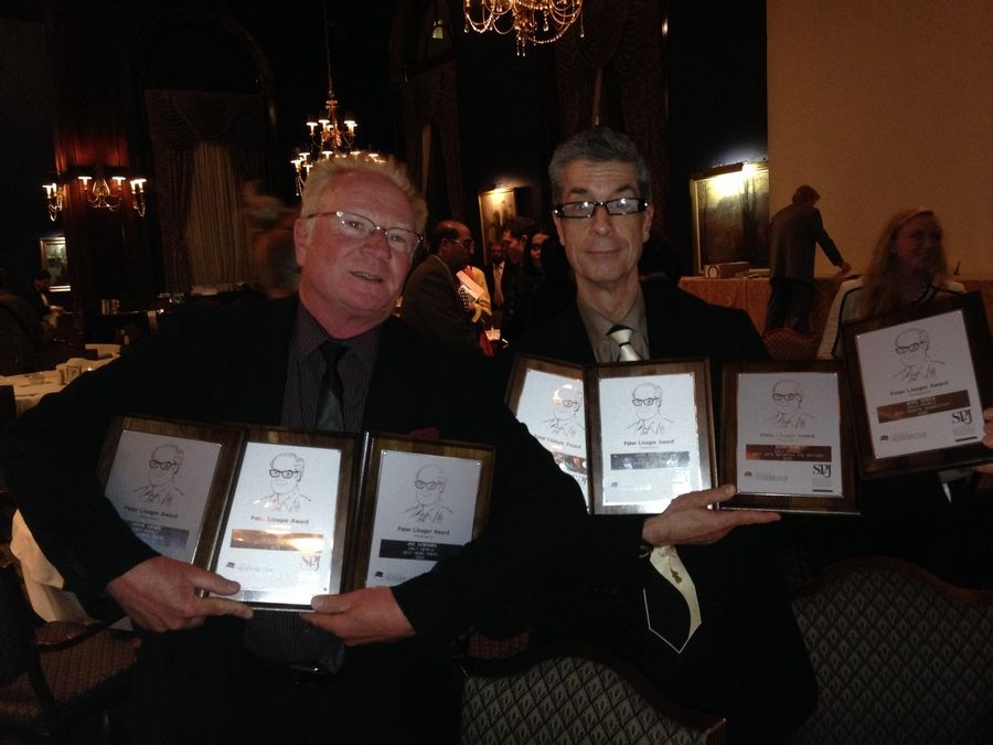 Daily Herald photographer Bob Chwedyk and film critic Dann Gire hold the seven Peter Lisagor awards the newspaper's staff won Friday night in Chicago.