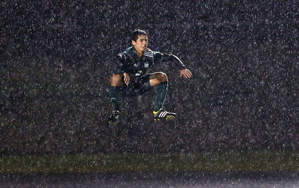 """Goalie's leap"" -- As photojournalists we have to be ready to shoot in all weather conditions. This sectional boys soccer matchup between Grayslake Central and Antioch took place in a total downpour. The dark background accentuates the rain as this defender from Grayslake Central tries to stay warm by jumping."