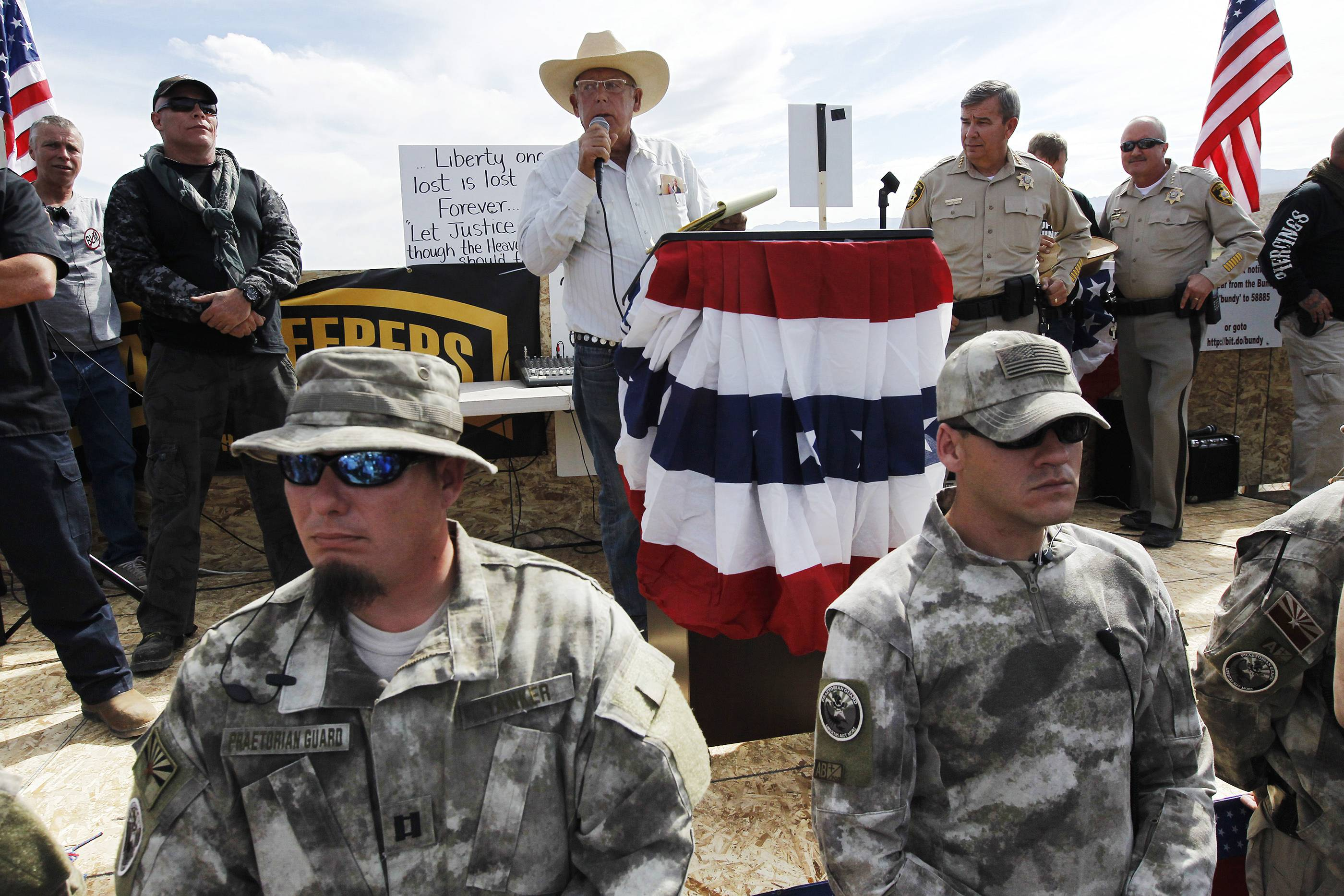 Rancher Cliven Bundy, center, addresses his supporters along side Clark County Sheriff Doug Gillespie, right, while being guarded by self-described militia members in the foreground.