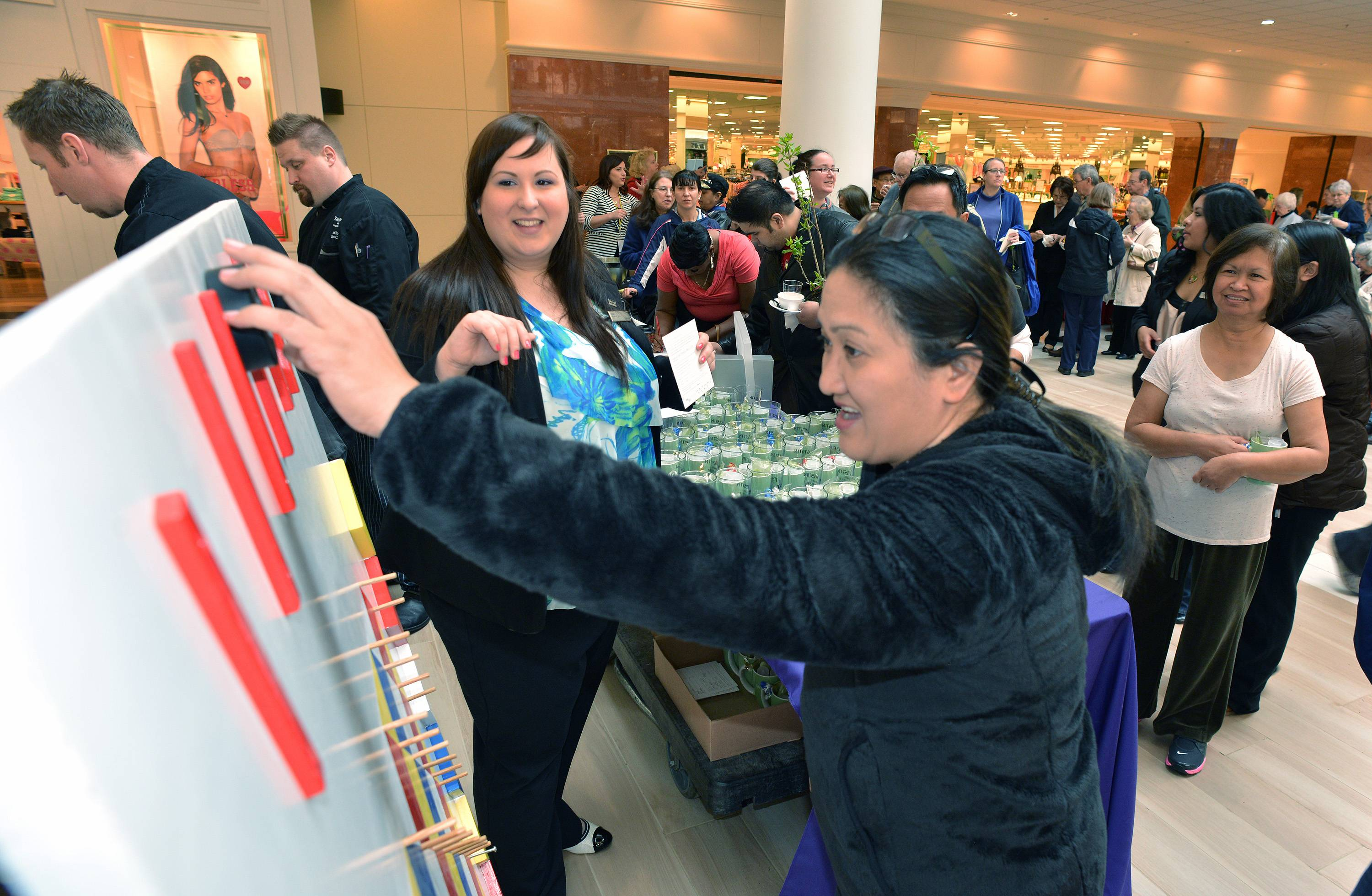 Julia Kochan, center left, from the Westin hotel, helps Agnesita Deasis, center right, play Plinko to try to win a free night at The Westin. Deasis didn't win, but she went home with a coffee mug filled with samples from the hotel. The activity was part of Yorktown Center's ribbon-cutting event Friday to celebrate the mall's $20 million renovation project.