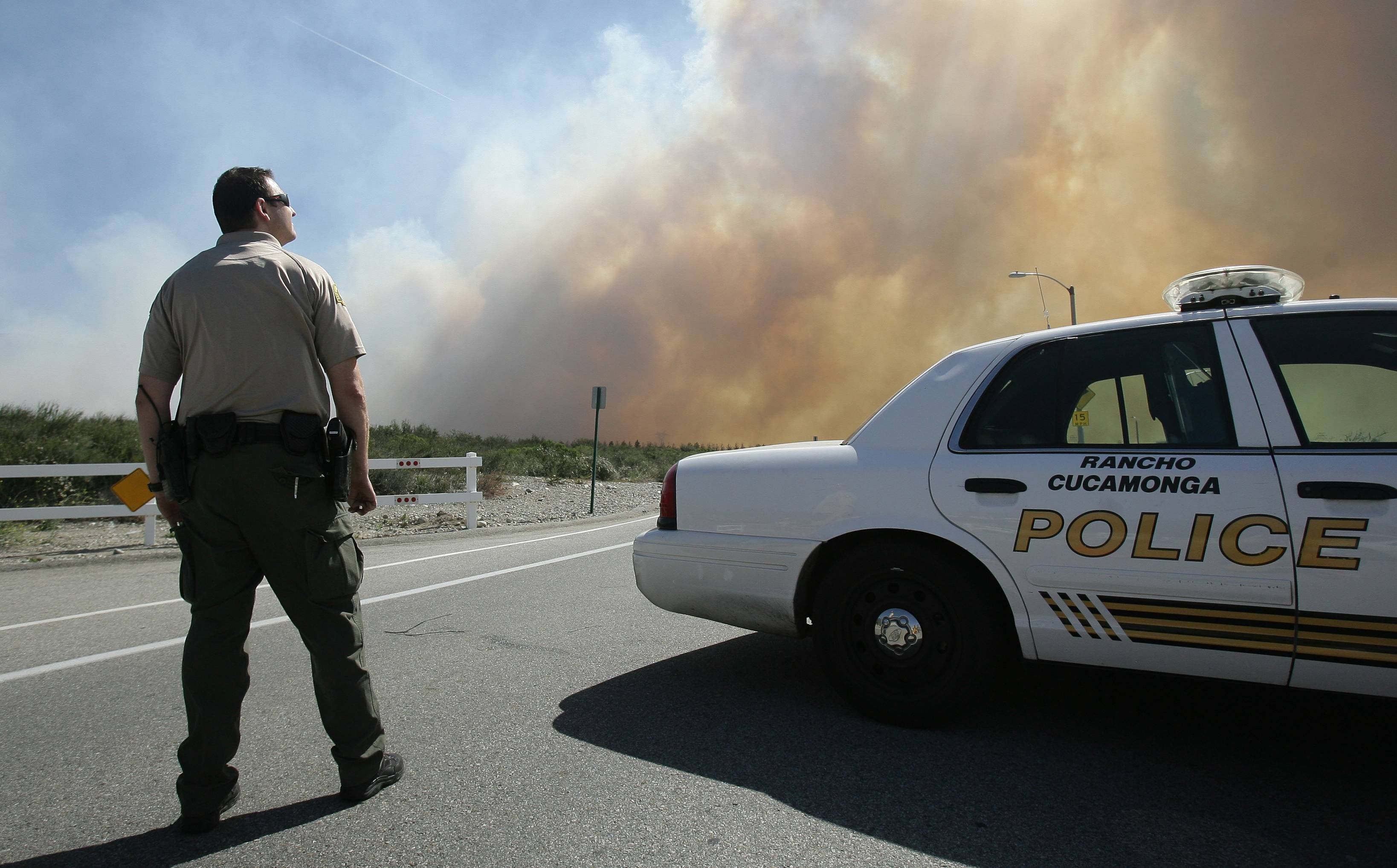 A San Bernardino Sheriff's deputy keeps an eye on a brush fire Wednesday burning in Day Creek near the Etiwanda Perserve in Rancho Cucamonga, Calif.