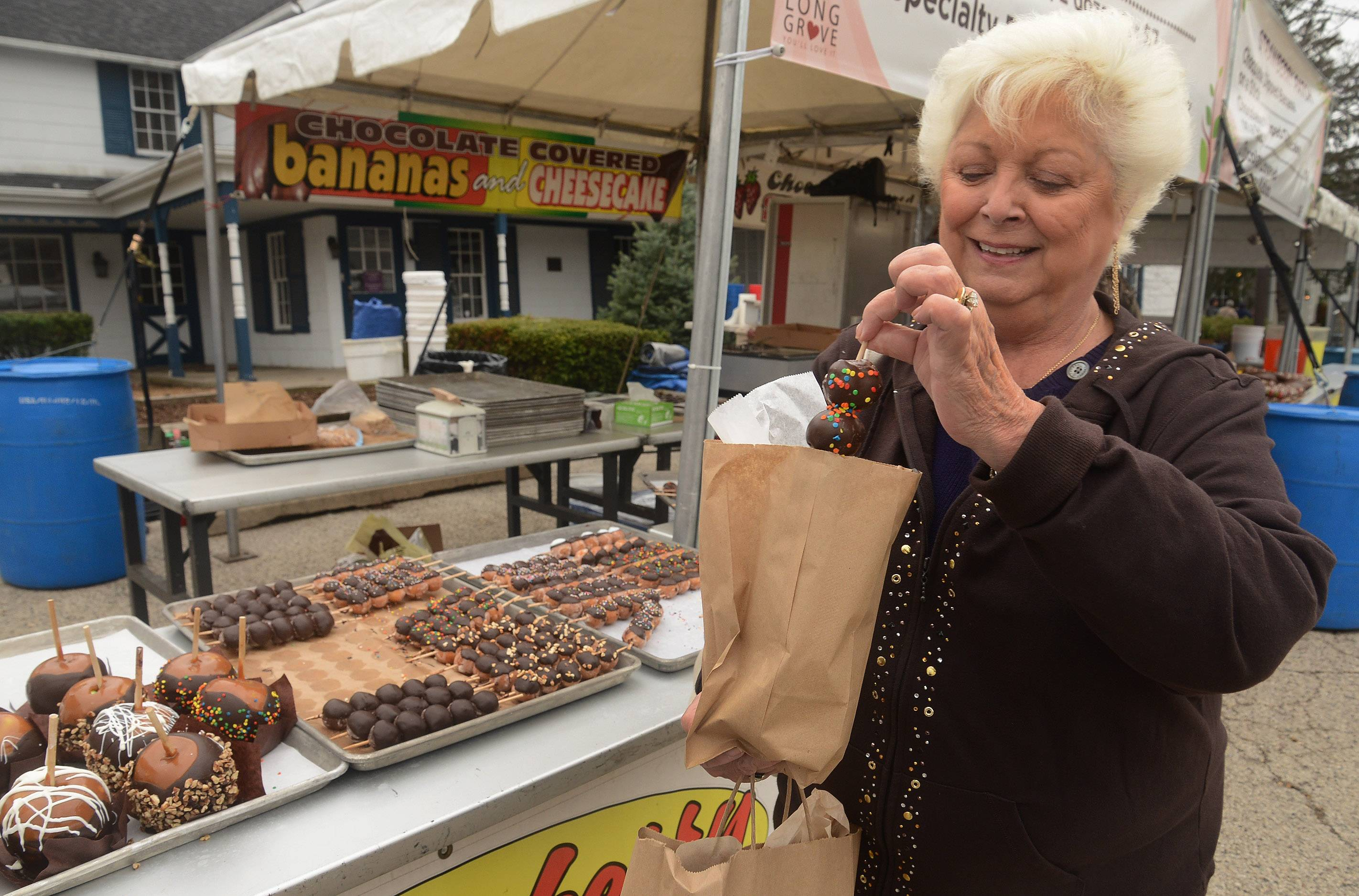 Carmie Foreman of Northbrook buys some chocolate-covered doughnut holes from the Strawberry Patch.