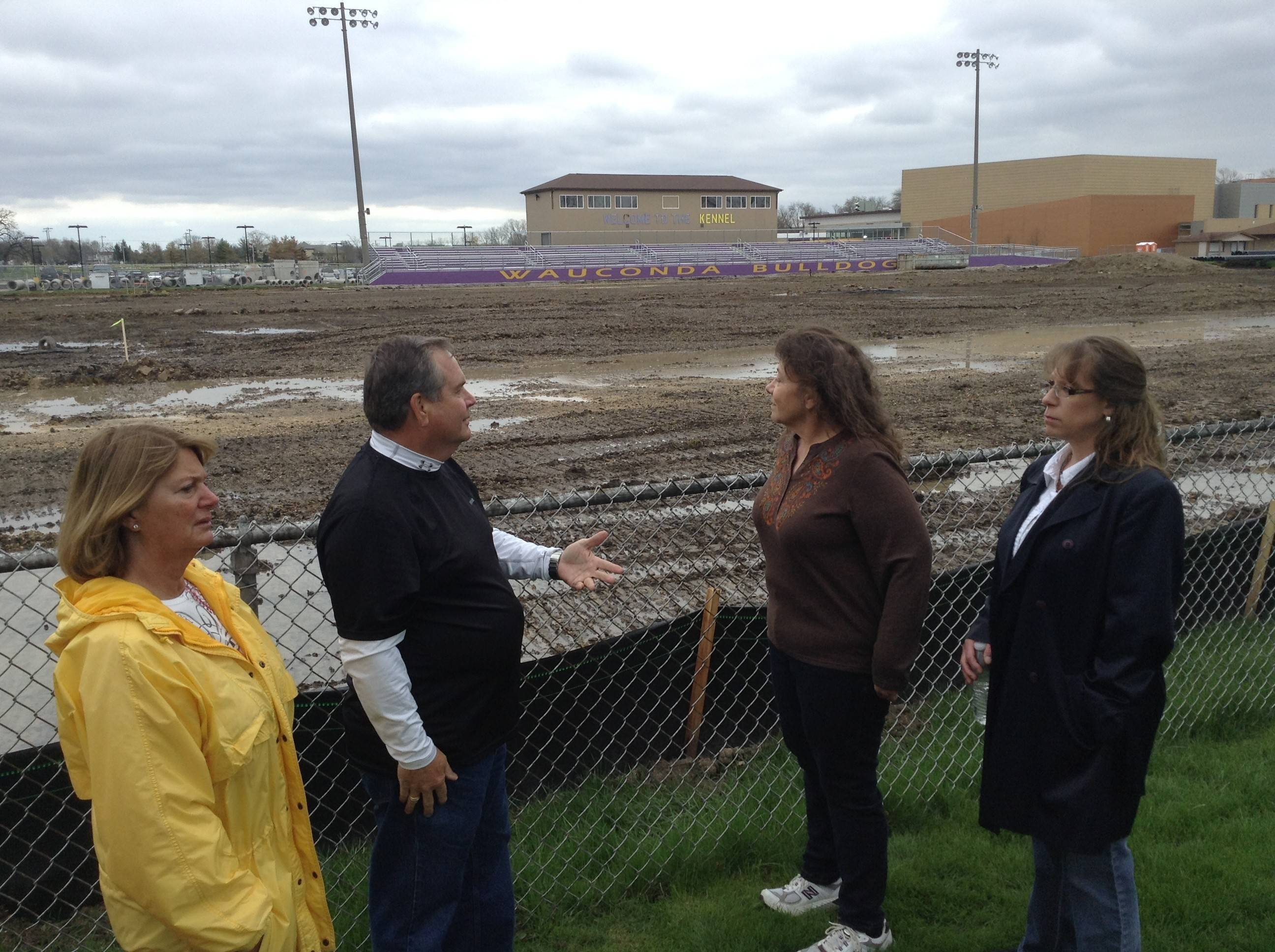 Wauconda resident Gary Thompson talks about the plan to install a new fence around the Wauconda High School football stadium as his wife, Cheryl, and neighbors Darlene Hayden and Jennifer Barr listen.