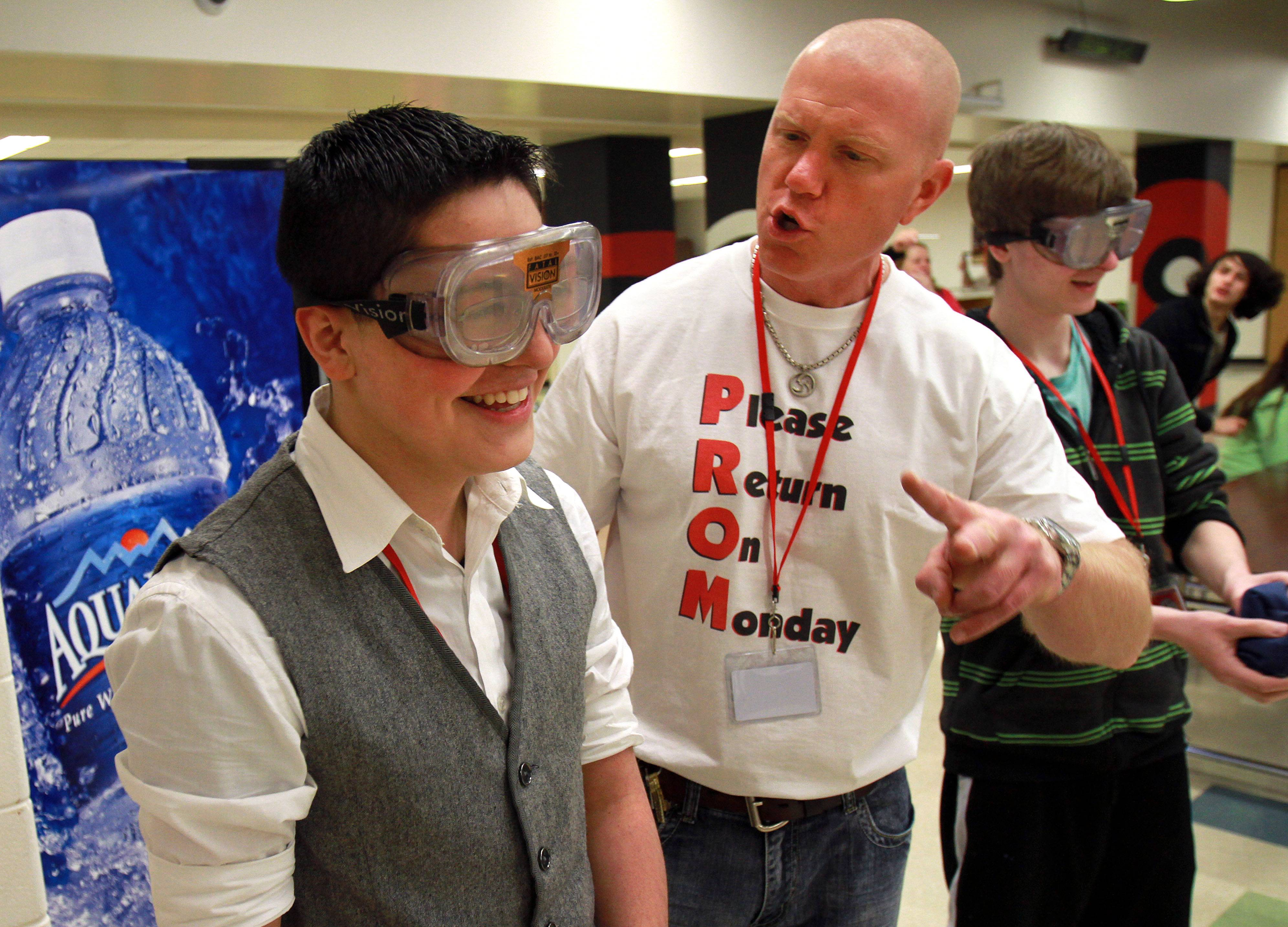 Grant High School Resource Officer Russell Zander, right, talks with freshman Isidro Villarrel as he tries to play baggo with goggles that simulate being intoxicated during a pre-prom event Friday at the Fox Lake school.