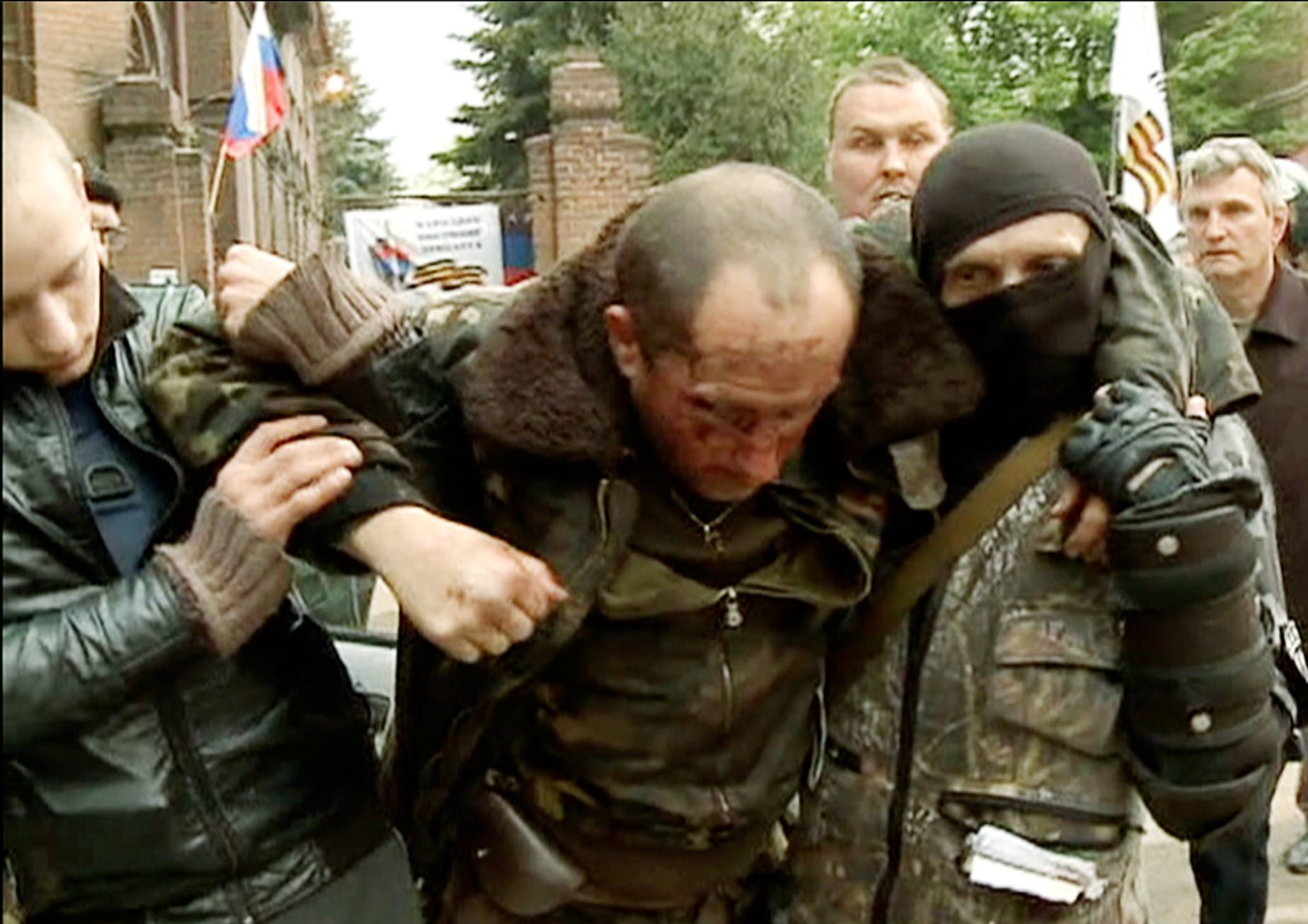An injured Ukrainian military helicopter pilot is assisted by pro-Russian activists after he was shot down in Slovyansk, eastern Ukraine, Friday May 2, 2014. Pro-Russia forces shot down two Ukrainian helicopters Friday as Ukraine launched its first major offensive against an insurgency that has seized government buildings in the east.