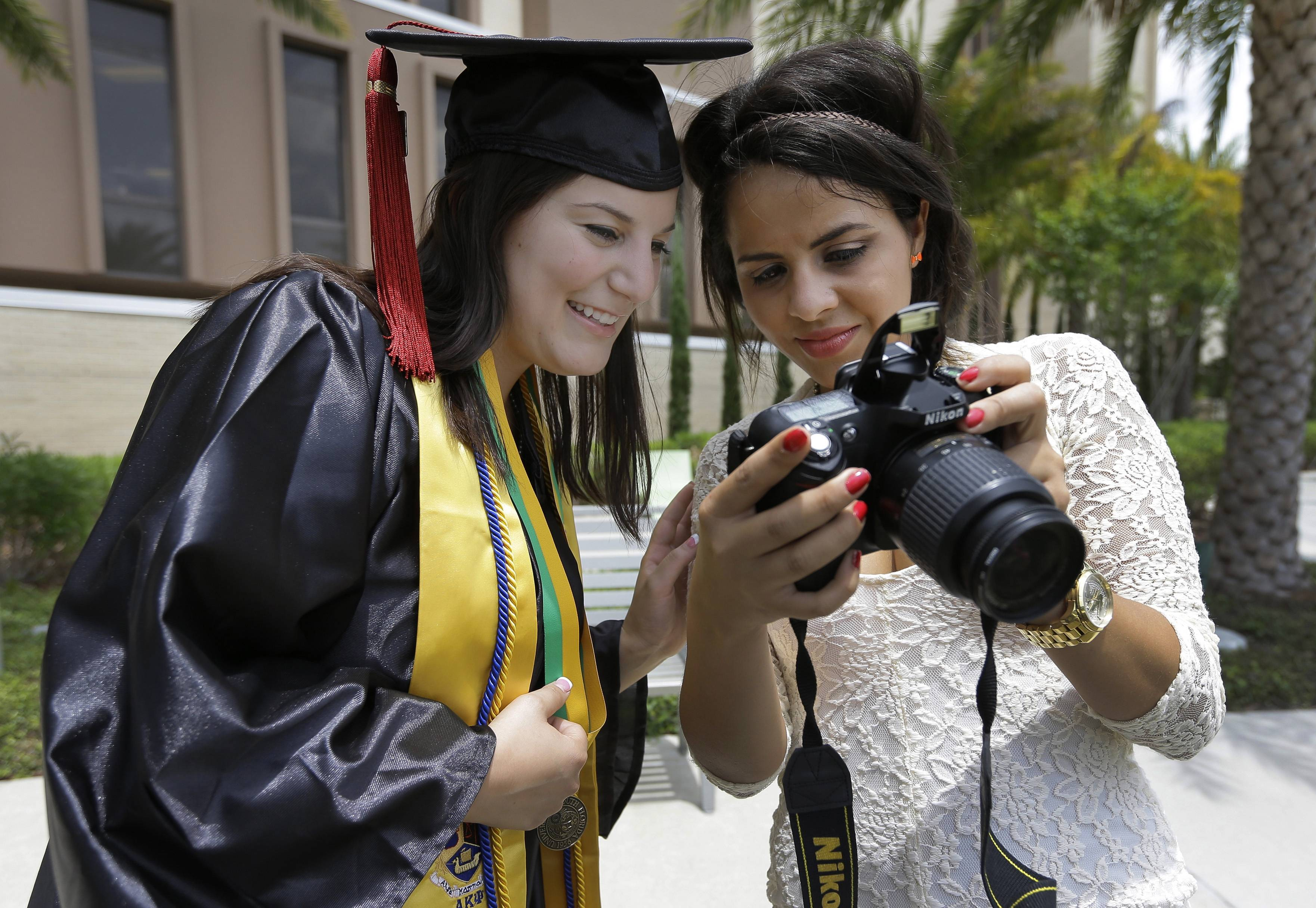 University of South Florida graduating seniors Kyra Ciotti, 22, of Tampa, Fla., left, and Rita Sibaja, 24, of Winter Haven, Fla., look at photos that Rita took of Kyra in her cap and gown Tuesday, April 29, 2014, in Tampa, Fla. The university has banned graduates from taking selfies while on the stage to collect their diplomas during graduation exercises.