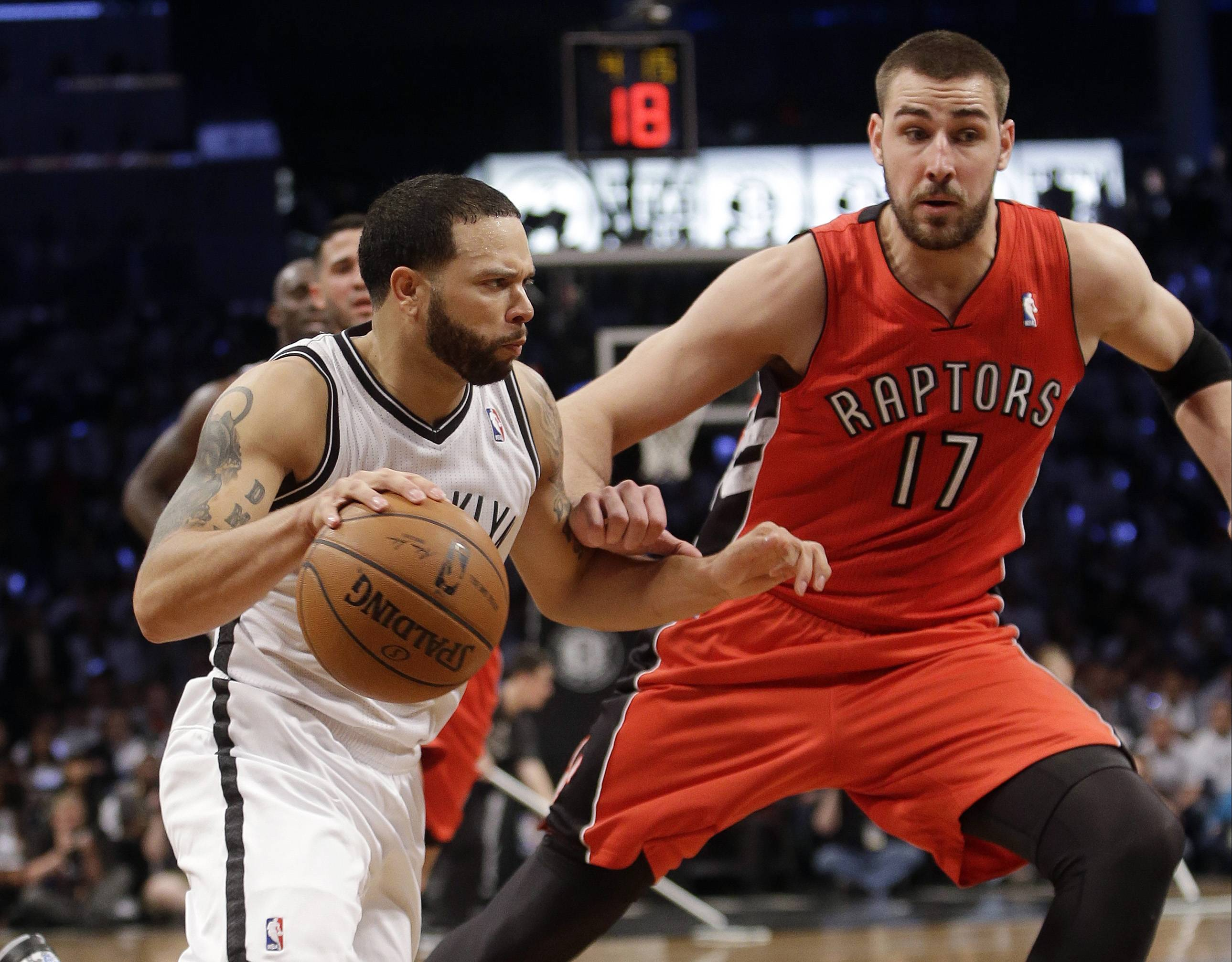 Brooklyn Nets' Deron Williams drives past Toronto Raptors' Jonas Valanciunas, right, during the second half of Game 6 of the opening-round NBA basketball playoff series Friday, May 2, 2014, in New York. The Nets won the game 97-83.