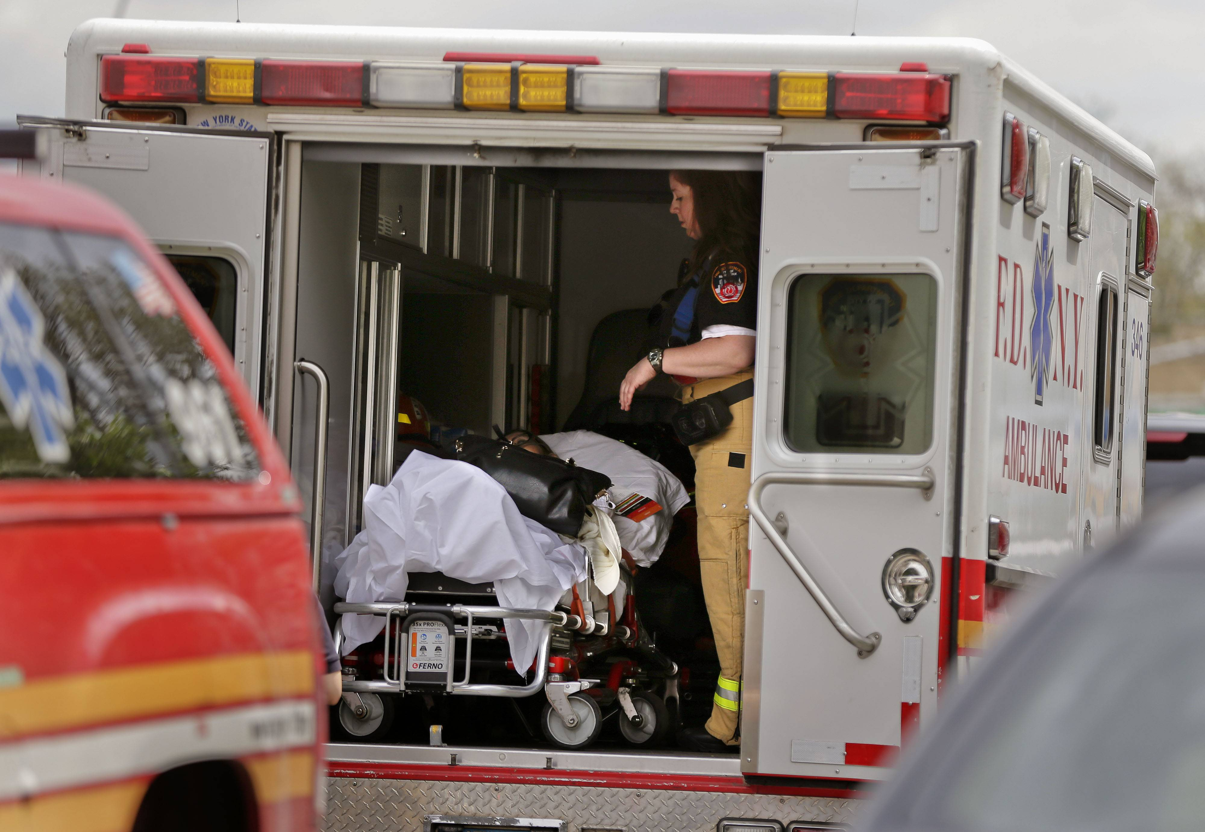 A New York City fire department EMT prepares to transport a woman who was evacuated from a subway train after it derailed Friday in the Queens borough of New York.