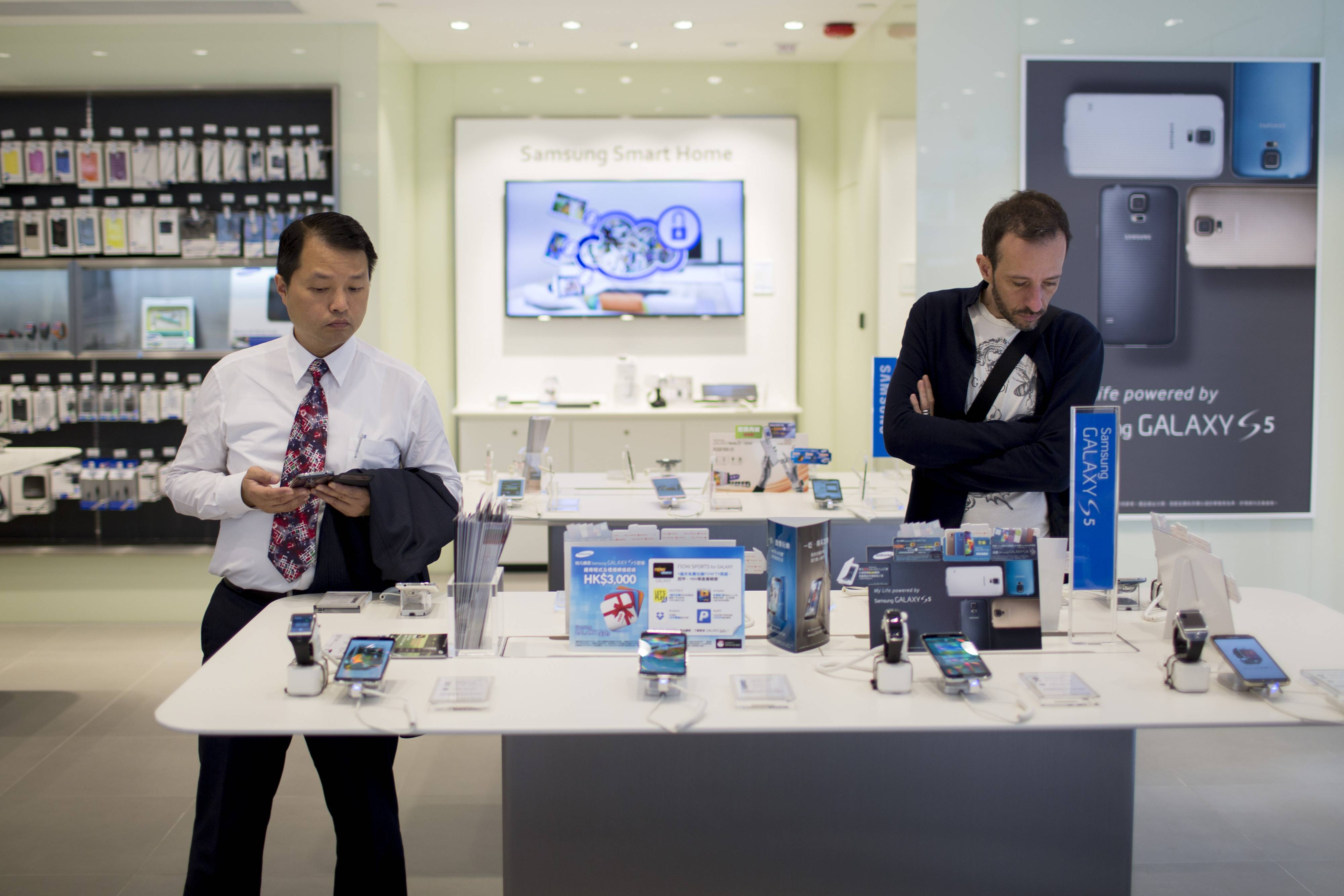 Customers browse Samsung Electronics Co. Galaxy S5 smartphones at a Samsung retail store in the Central district of Hong Kong, China.